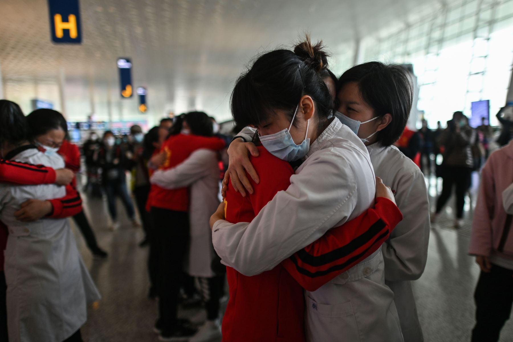 El personal médico de la provincia de Jilin abraza a las enfermeras de Wuhan después de trabajar juntas durante el brote de coronavirus, aquí durante una ceremonia antes de partir cuando el aeropuerto de Tianhe se reabrió en Wuhan. Foto: AFP
