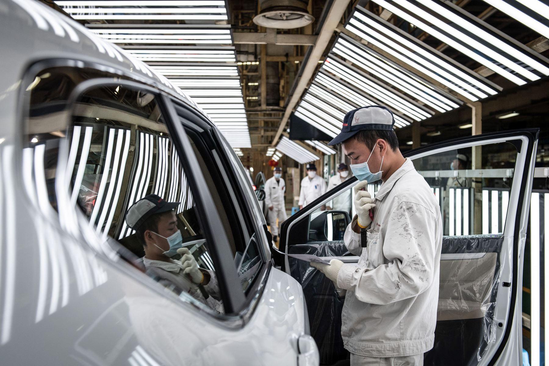 Un empleado con una máscara facial trabajando en una línea de ensamblaje en una planta de automóviles de Dongfeng Honda en Wuhan. Foto: AFP