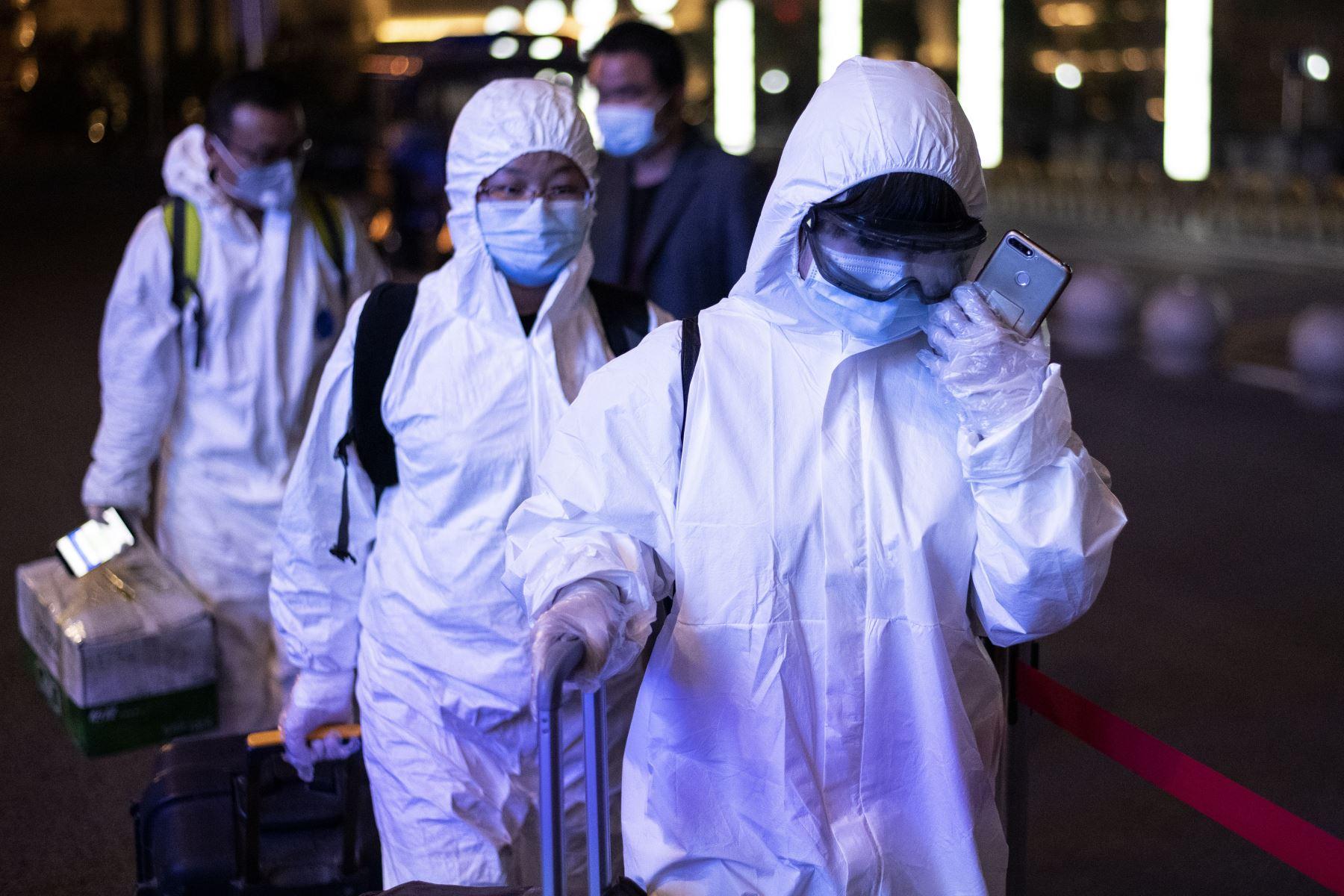 Pasajeros usan traje de materiales peligrosos cuando llegan a la estación de tren Wuhan Wuchang en Wuhan, para salir de la ciudad en la provincia central de Hubei de China. Foto: AFP