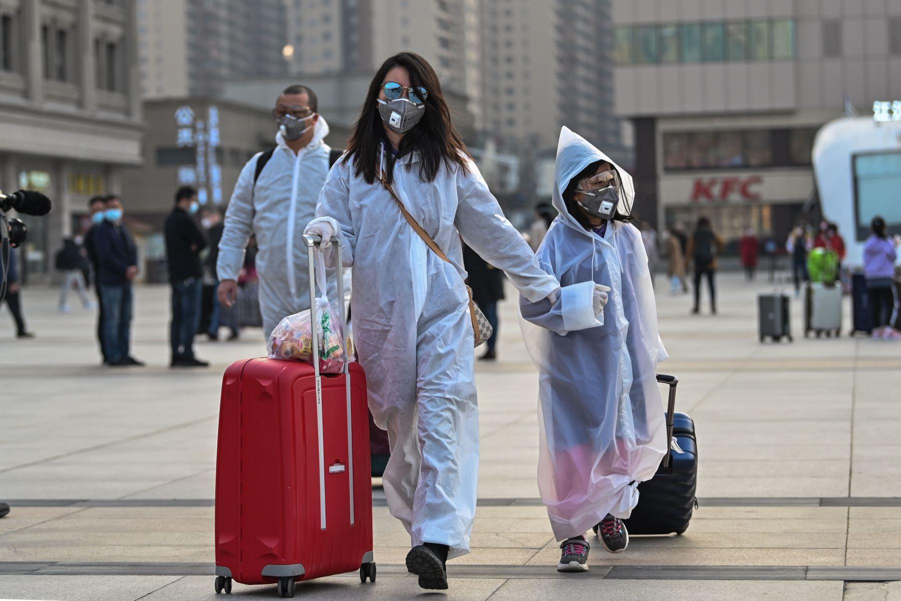 Las personas con máscaras y ropa protectora llegan a la estación de tren de Hankou en Wuhan, para abordar uno de los primeros trenes que salen de la ciudad en la provincia central de Hubei de China. Foto: AFP