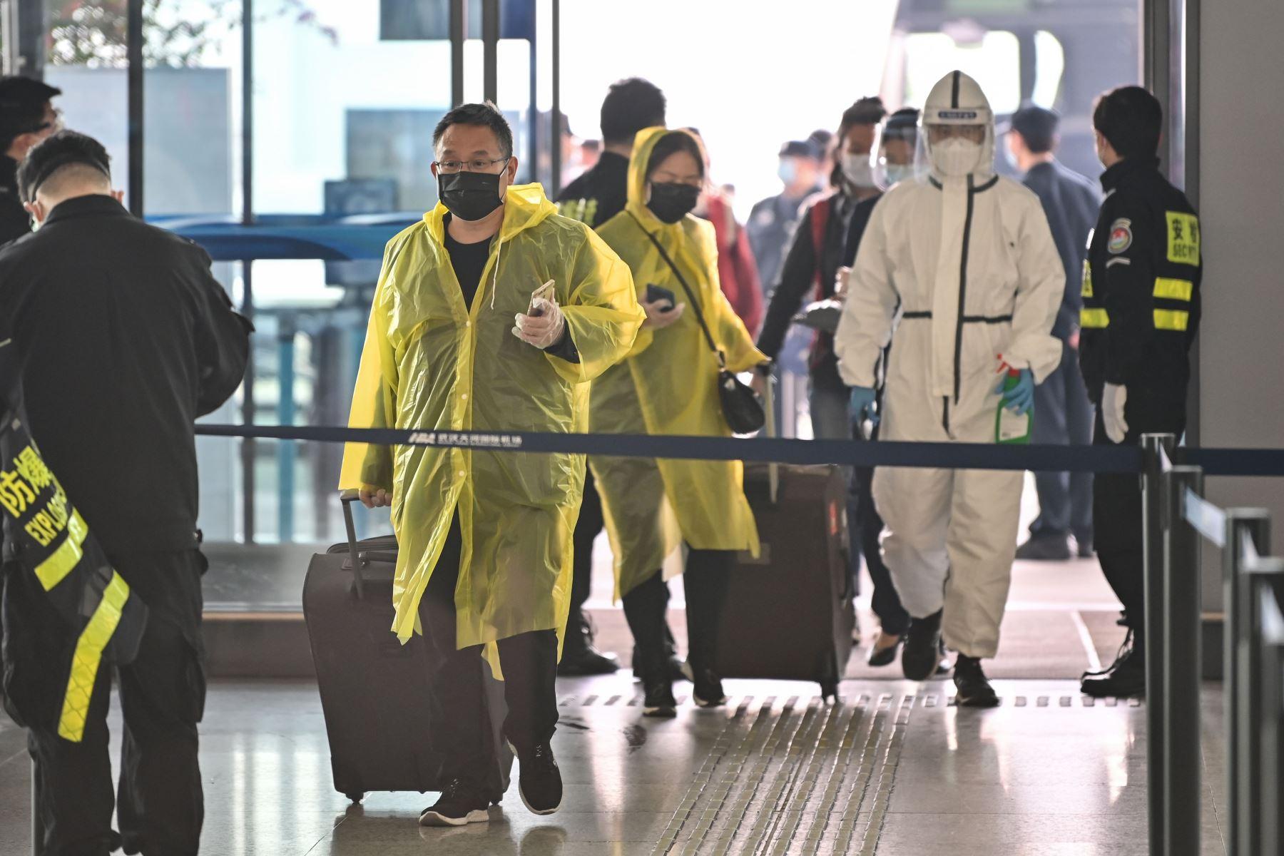 Los pasajeros que usan equipo de protección llegan al aeropuerto de Tianhe después de su reapertura, en Wuhan, en la provincia central china de Hubei. Foto: AFP