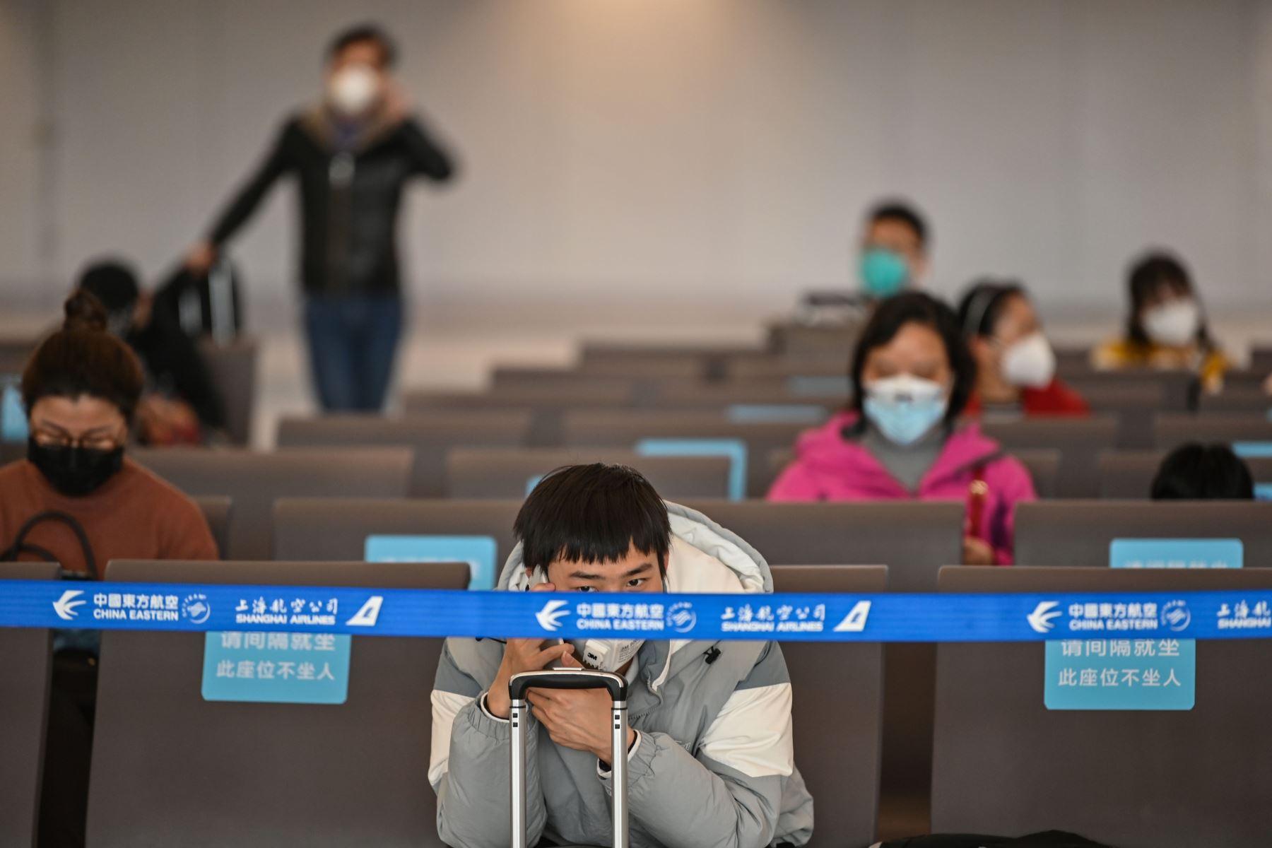 Los pasajeros con máscaras faciales se sientan en el aeropuerto de Tianhe después de que reabrió en Wuhan, en la provincia central china de Hubei. Foto: AFP