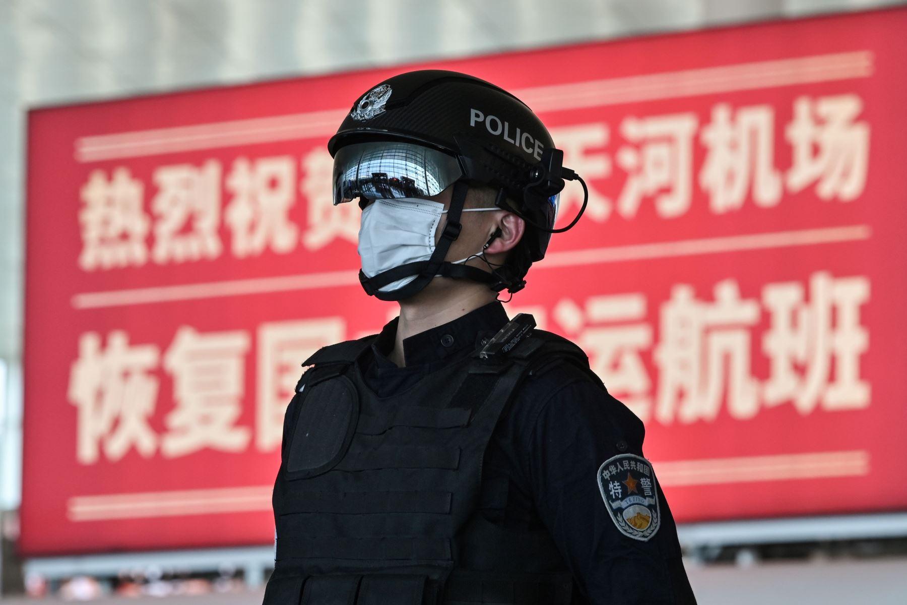 Un oficial de policía con una máscara facial hace guardia en el aeropuerto de Tianhe después de que fue reabierto en Wuhan, en la provincia central de Hubei, China. Foto: AFP