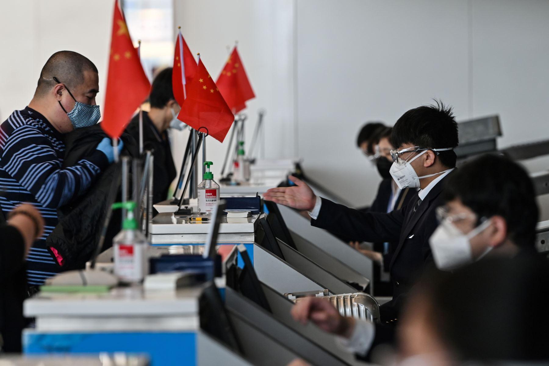 Un pasajero con una máscara facial es visto en el mostrador del aeropuerto de Tianhe después de que fue reabierto en Wuhan. Foto: AFP
