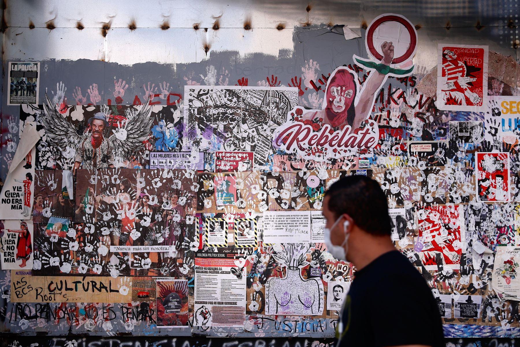 Hombre camina frente a una pared llena de grafitos y avisos durante la jornada de cuarentena obligatoria para frenar el avance de covid-19, en el centro de Santiago (Chile). Foto: EFE
