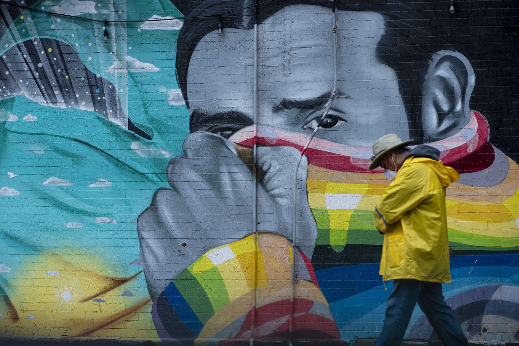 Un hombre con una máscara pasa un mural el de 2020 en la ciudad de Nueva York. Foto: AFP