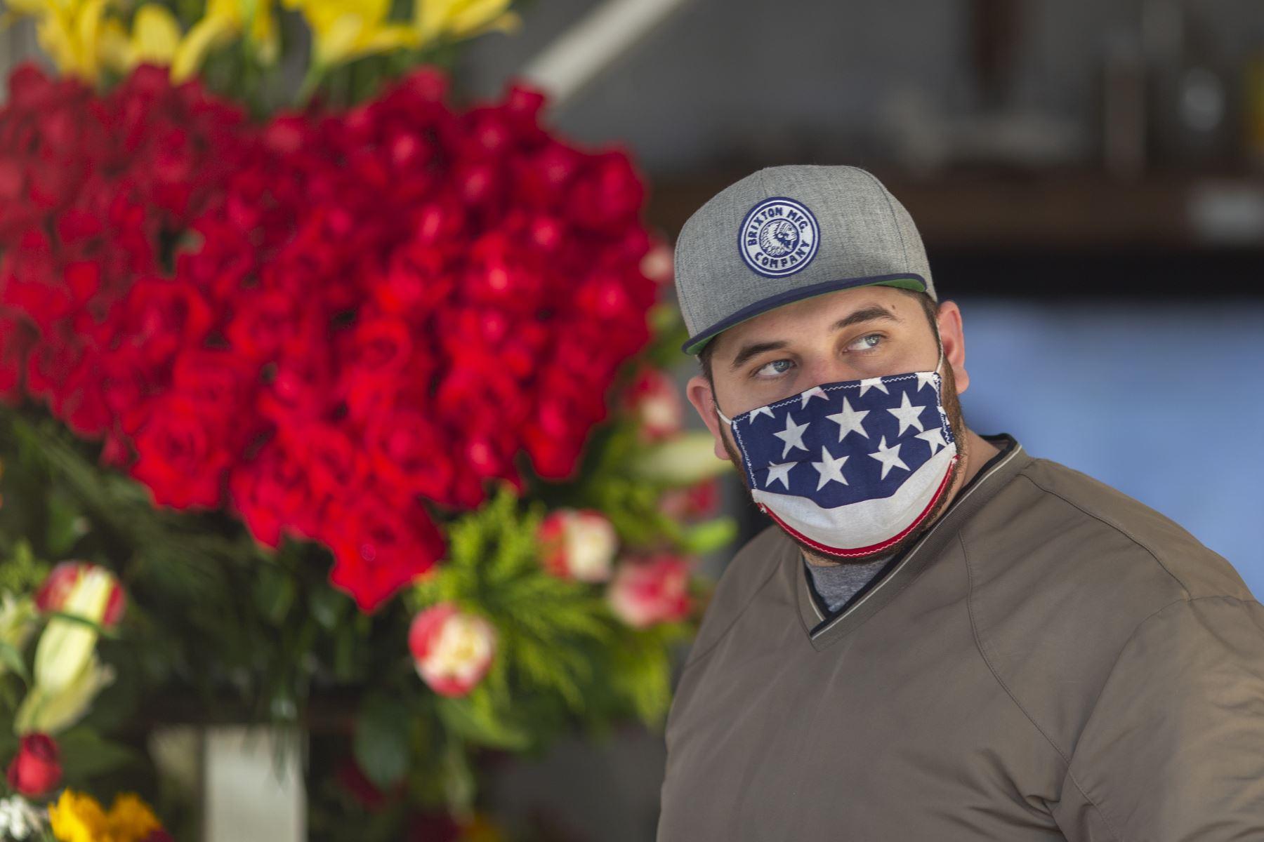 Un hombre camina con una mascarilla patriótica mientras las empresas en el distrito de las flores en Skid Row reabran sus negocios. Foto: AFP