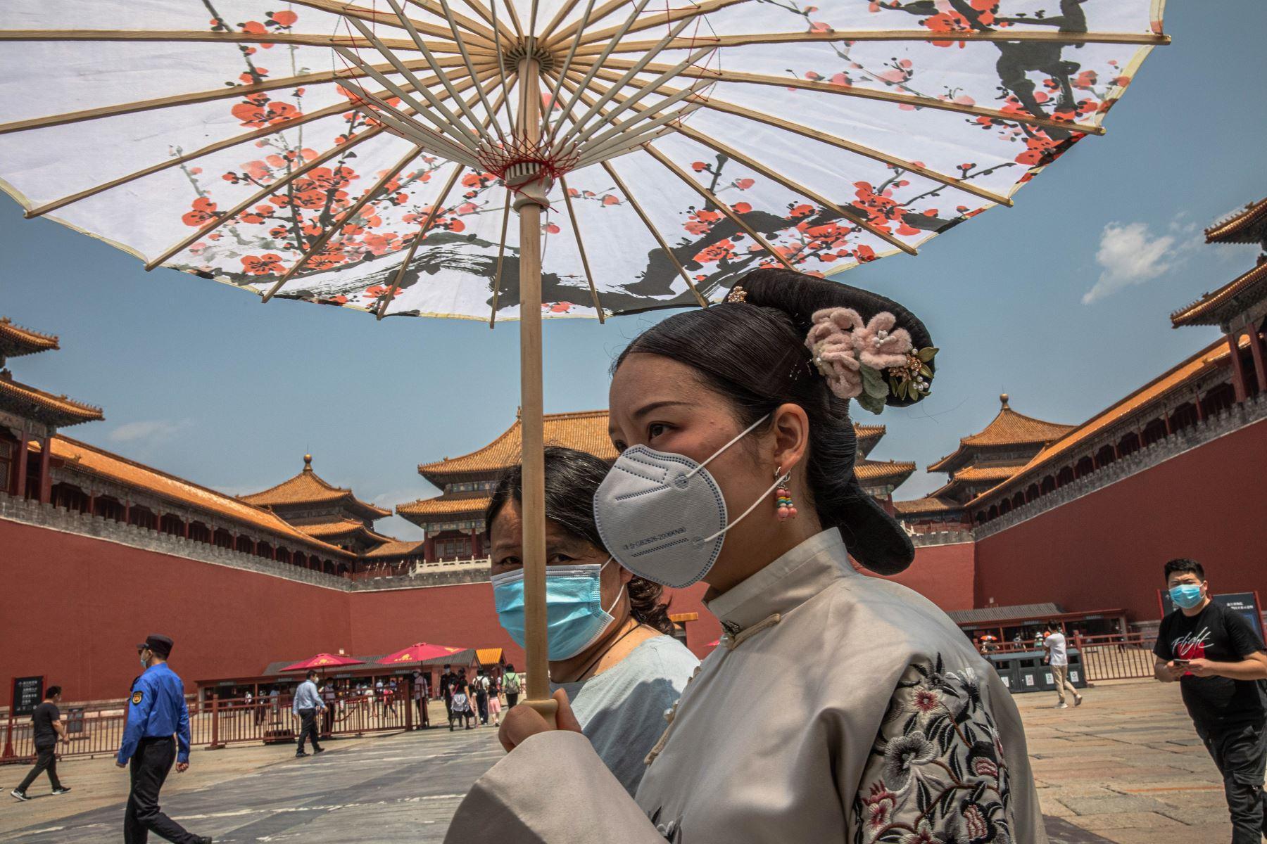 os mujeres con mascarillas caminan por la entrada de la Ciudad Prohibida el primer día del Congreso Nacional del Pueblo (APN) de China en Beijing. Foto: EFE