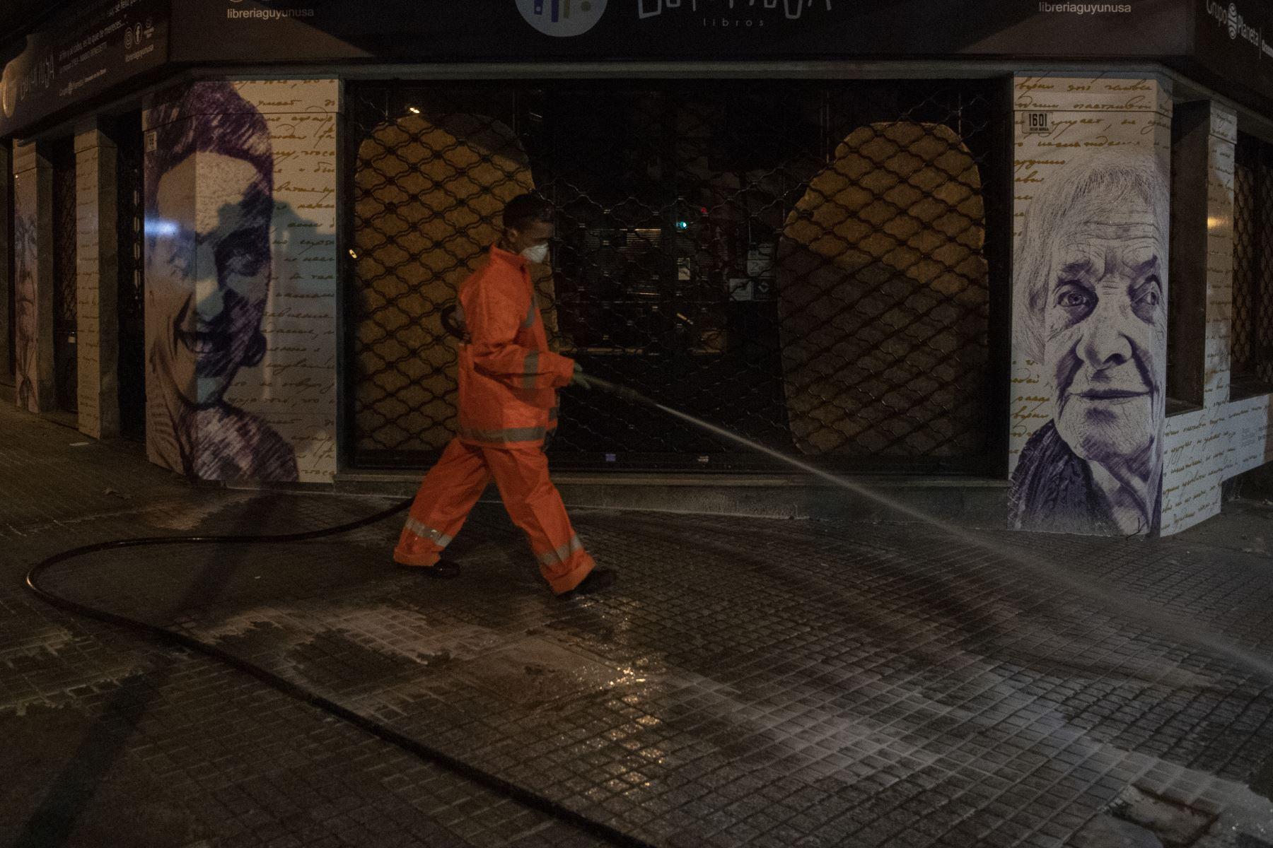 Un trabajador del municipio desinfecta la calle Tristan Narvaja contra la propagación del nuevo coronavirus en Montevideo. Foto: AFP