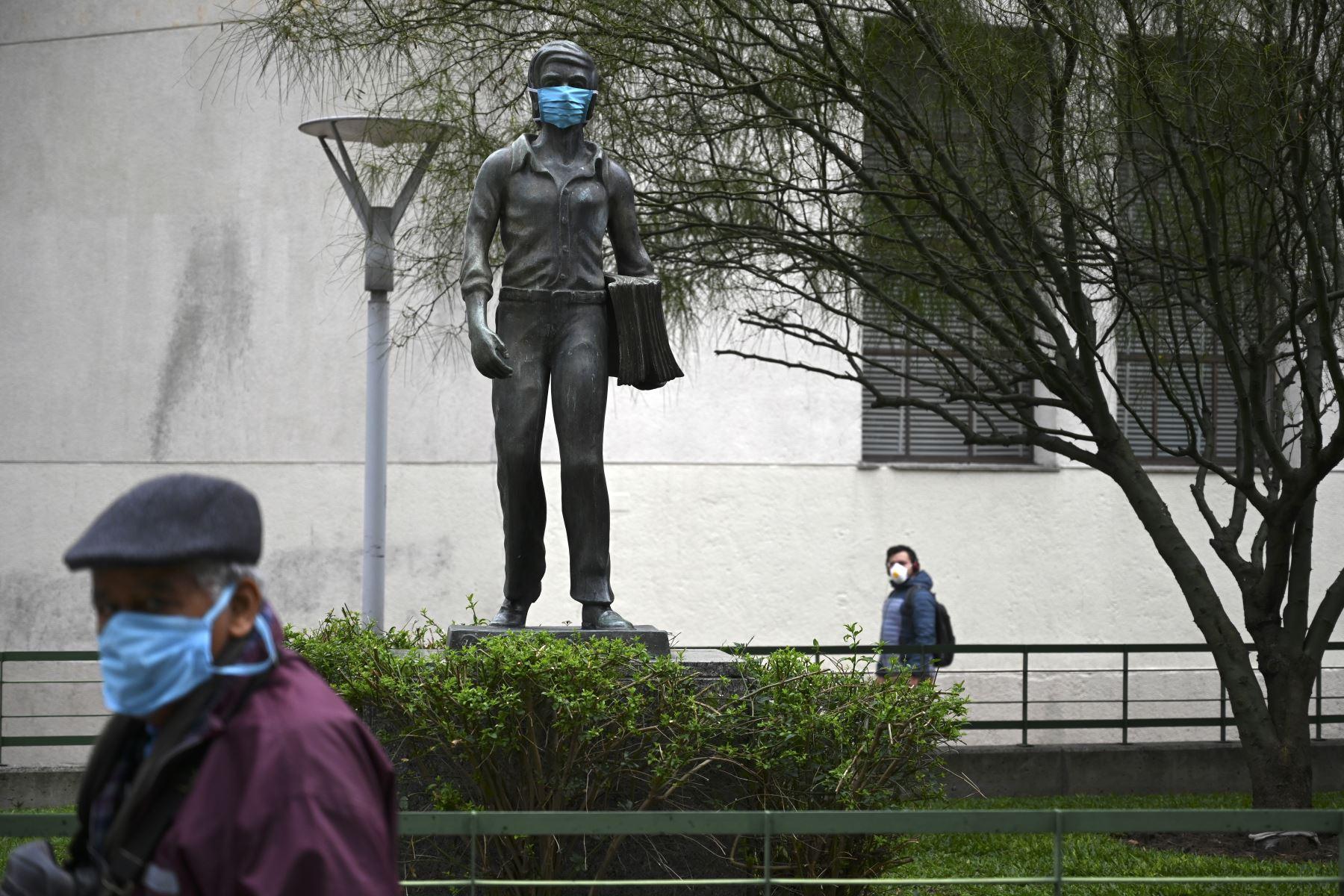 Una escultura que representa a un repartidor de periódicos usa una máscara facial en Montevideo. Foto: AFP