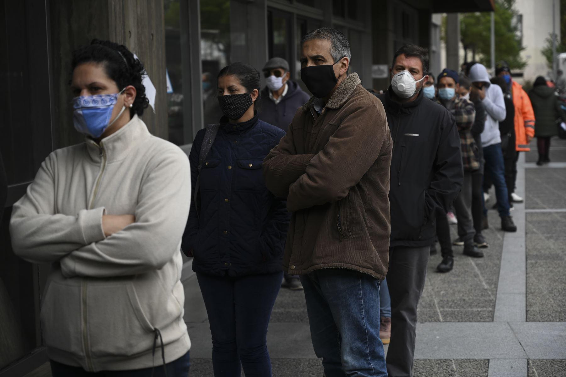 Personas con máscaras faciales se alinean frente al edificio de seguridad social de propiedad estatal uruguaya en Montevideo. Foto: AFP