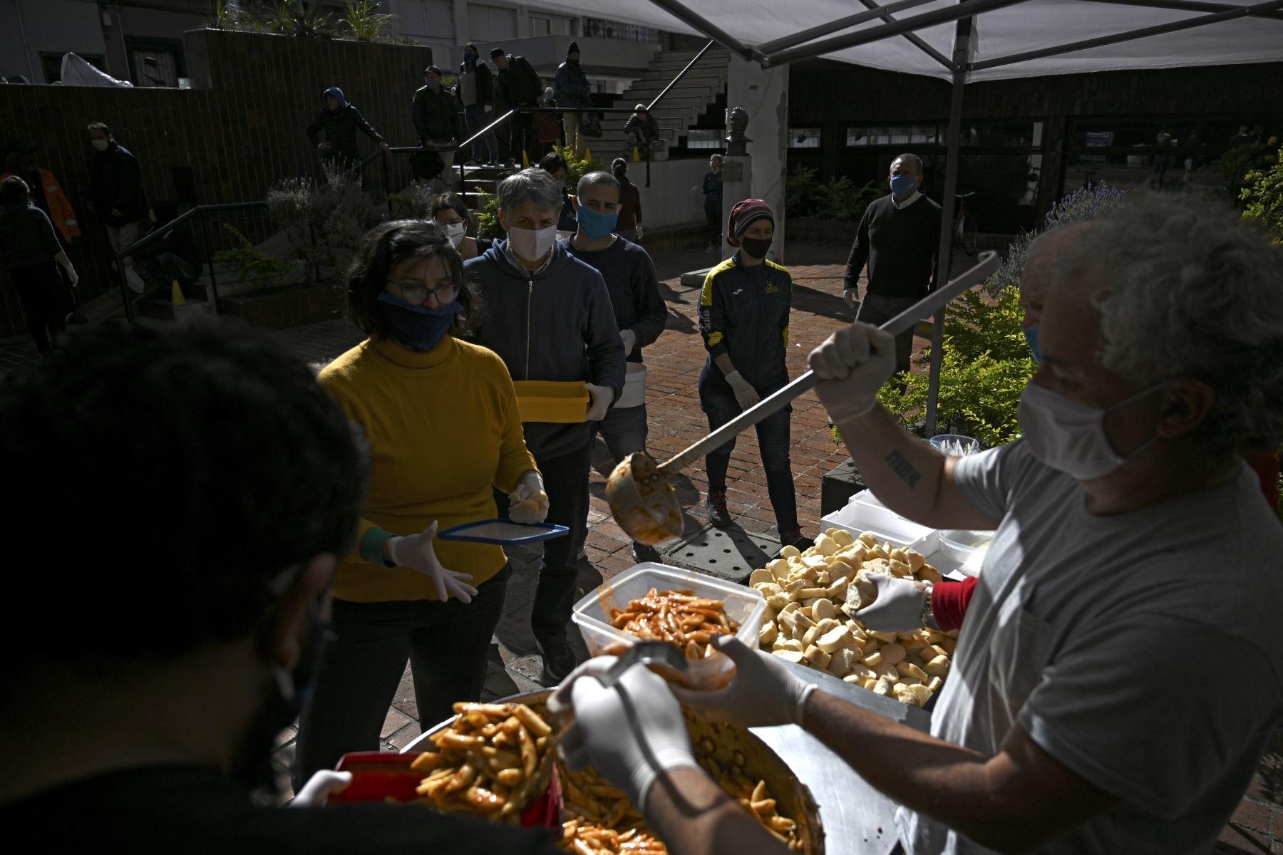 Un voluntario sirve una comida mientras la gente hace cola en un comedor popular en Montevideo. Foto: AFP