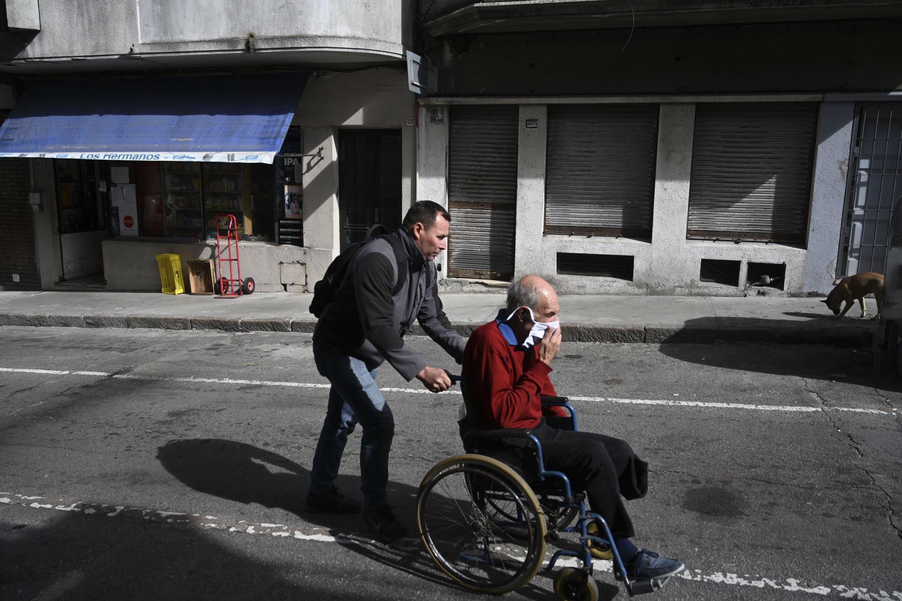 Un anciano con una máscara facial es empujado en su silla de ruedas en Montevideo. Foto: AFP