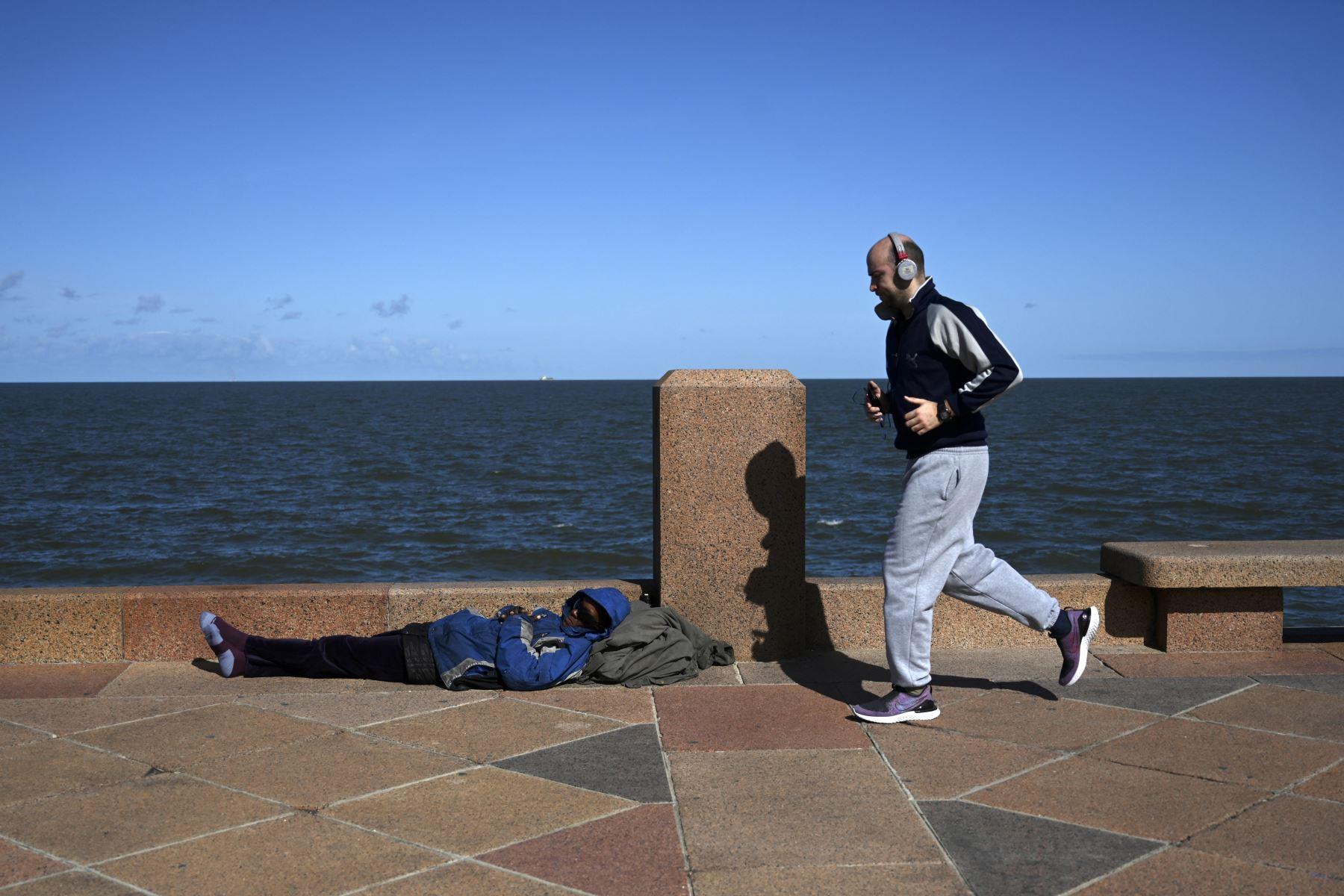 Un hombre corre y pasa junto a un hombre sin hogar a lo largo de la avenida Rambla de Montevideo. Foto: AFP