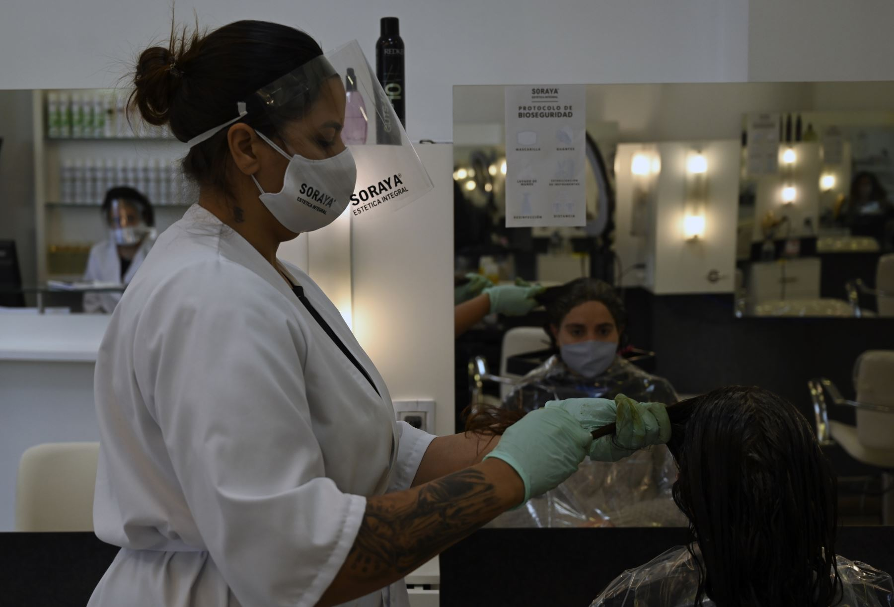 Un empleado usa un protector facial en un salón de peluquería en Montevideo. Foto: AFP