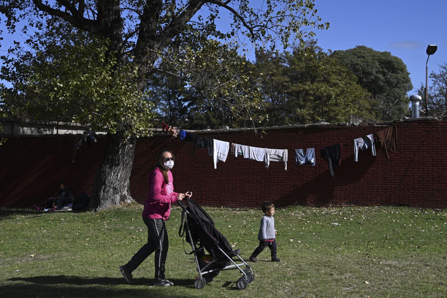 Una mujer usa una máscara facial mientras camina con su hijo en un parque en Montevideo. Foto: AFP
