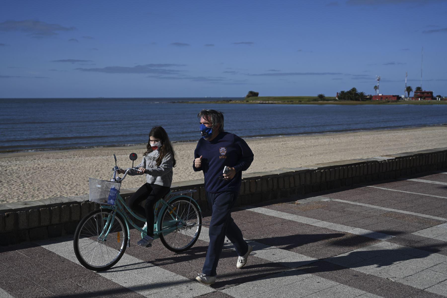 Un hombre y su hija usan máscaras faciales mientras hacen ejercicio a lo largo de la avenida costera de Montevideo Rambla. Foto: AFP