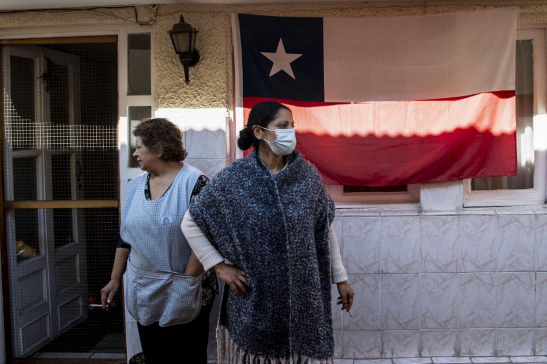 Una familia espera recibir una canasta de alimentos entregado por trabajadores municipales, en Chile. Foto: AFP