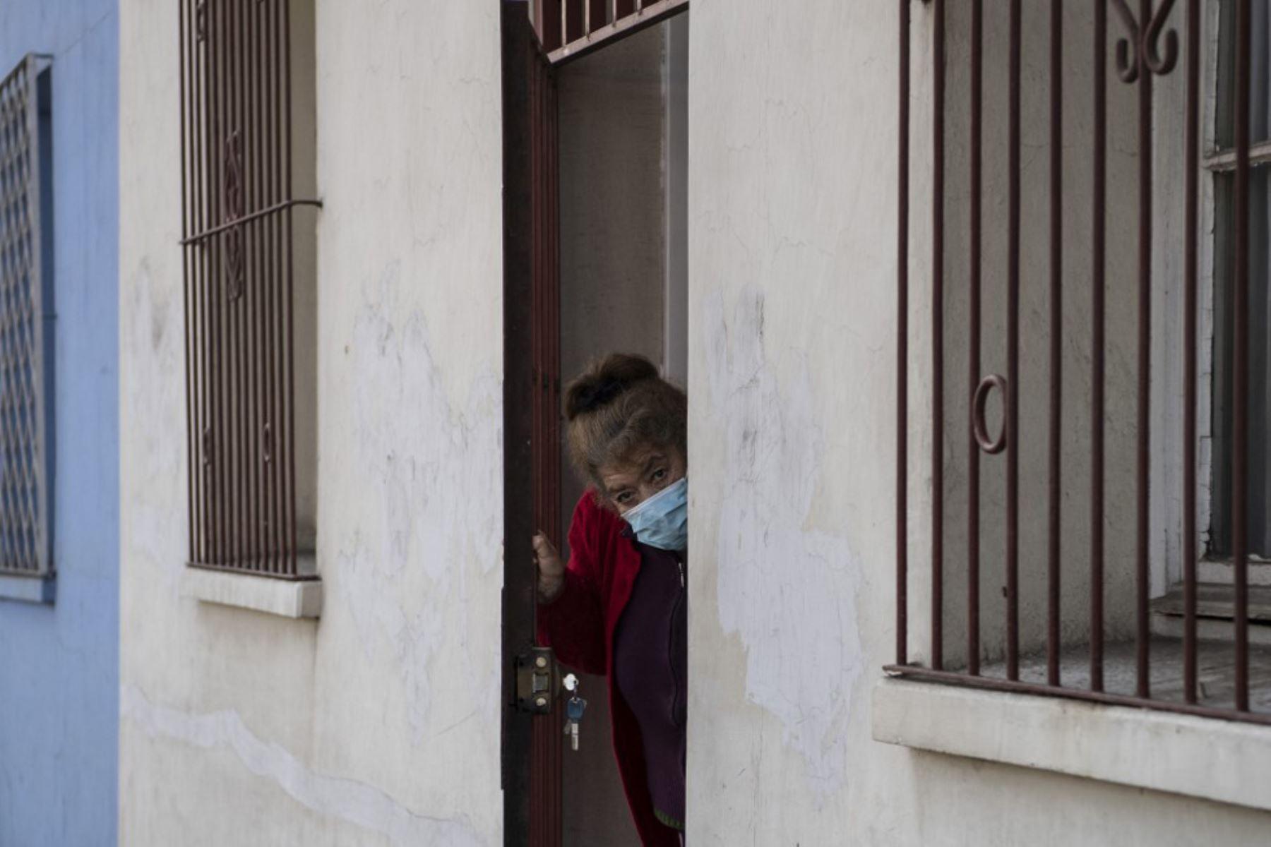 Una mujer con una máscara facial observa la entrega de cajas con alimentos por parte de trabajadores municipales a familias económicamente afectadas, en Chile. Foto: AFP