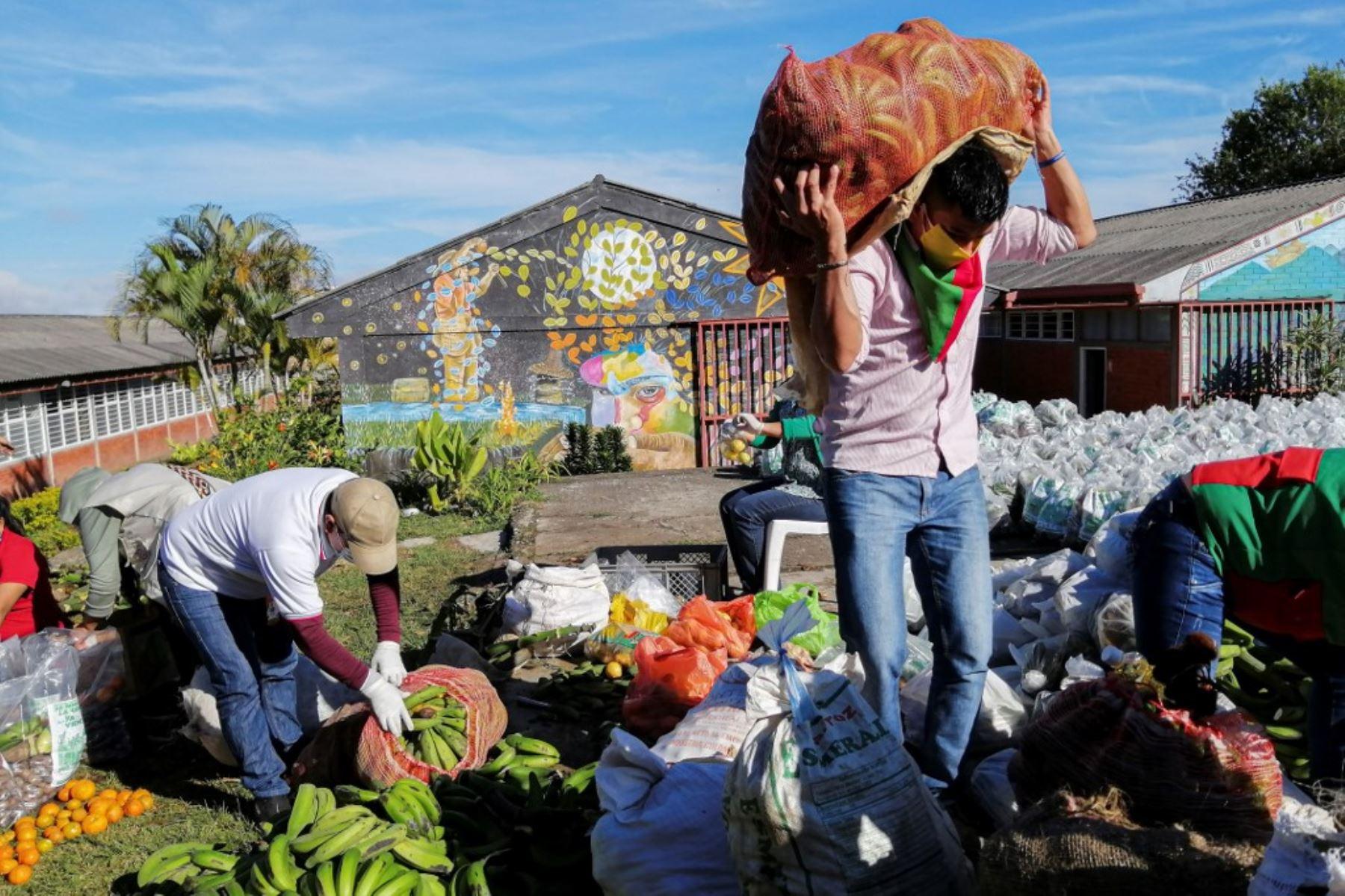 Un hombre carga alimentos recolectados de sus cultivos, para ser entregados entre familias vulnerables en Popayán, en Colombia. Foto: AFP