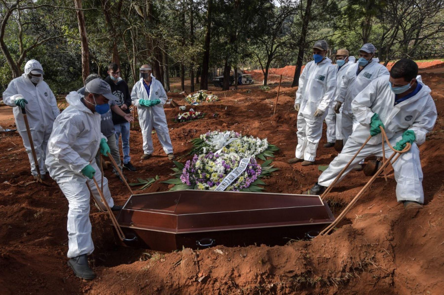 Un grupo empleados entierran el ataúd de una persona que murió por coronavirus en el cementerio de Vila Formosa, en las afueras de Sao Paulo, Brasil. Foto: AFP