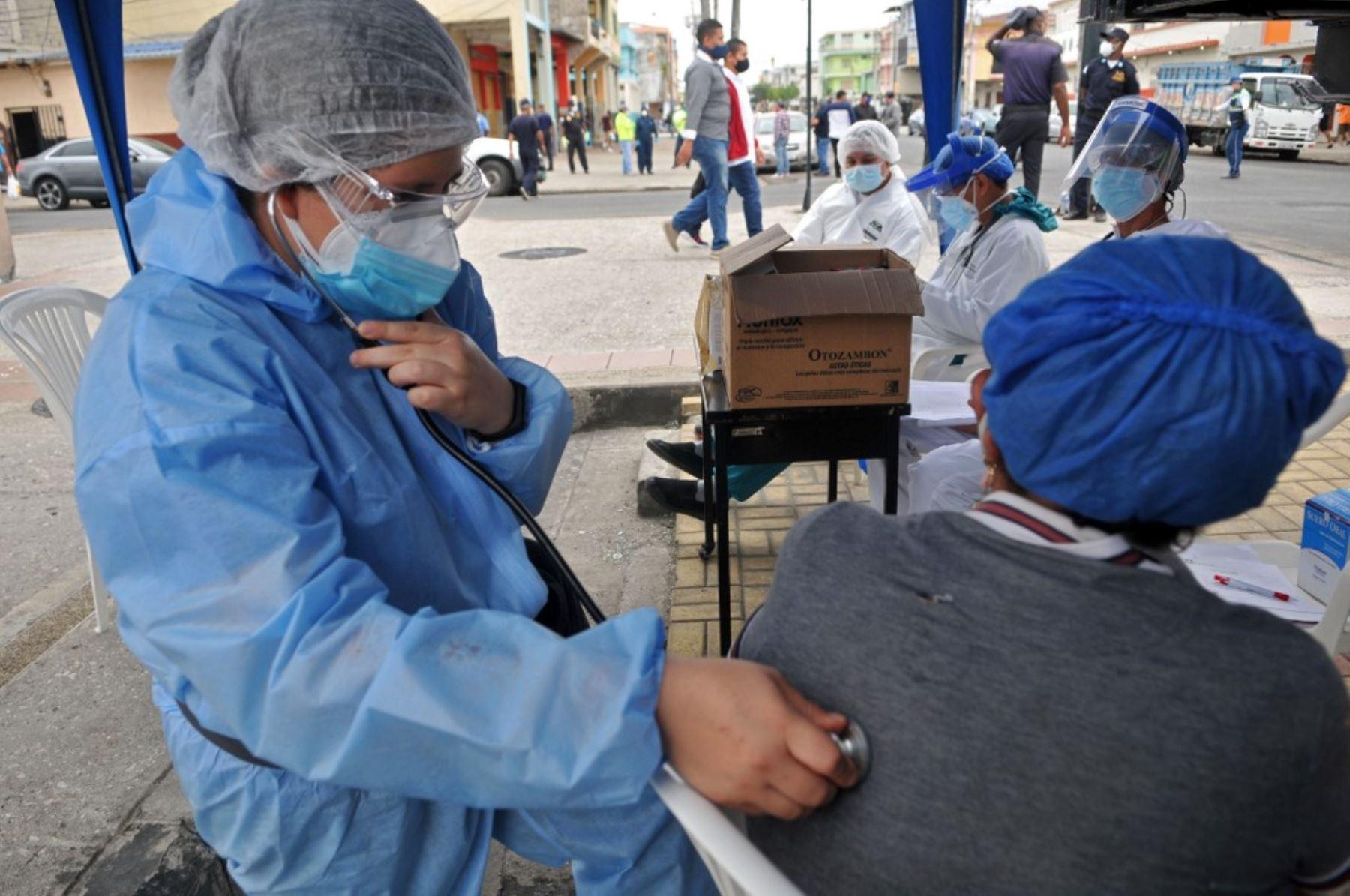 Un grupo de médicos de la Alcaldía de Guayaquil atiende a personas con problemas respiratorios en una carpa especial instalada en una calle de la ciudad. Foto: AFPl