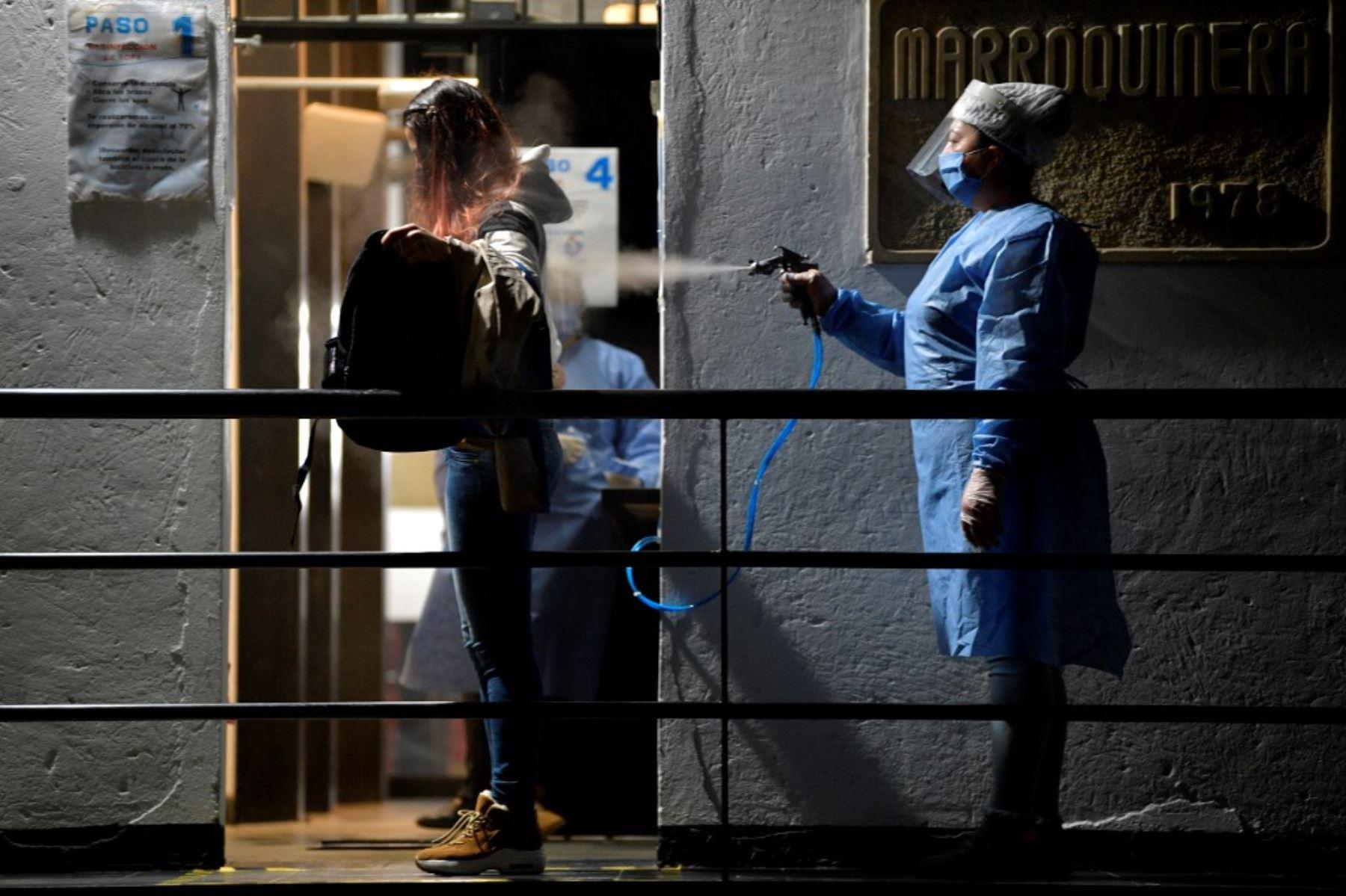 Una mujer desinfecta a un empleado como medida preventiva contra la propagación del nuevo coronavirus en Bogota, Colombia. Foto: AFP