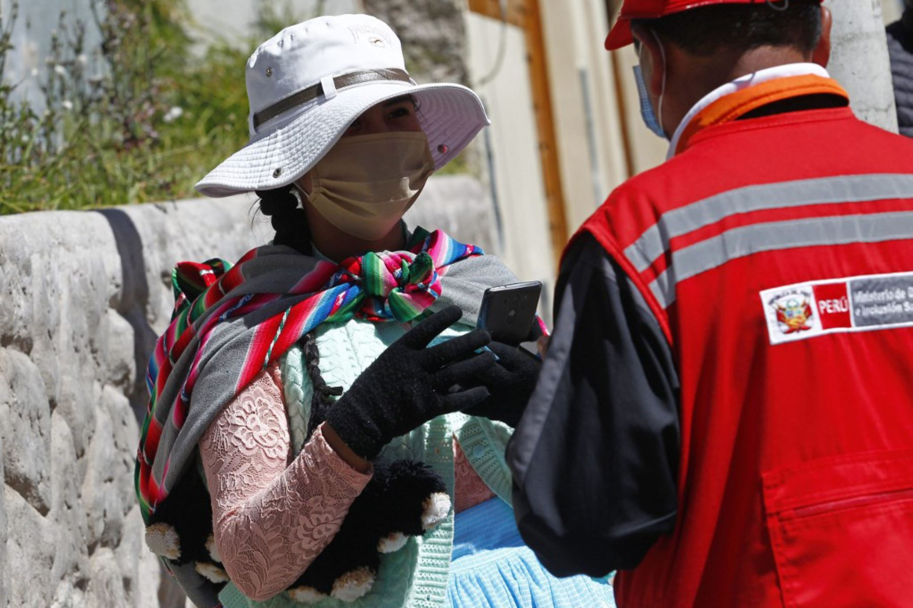 Una mujer con mascarilla es entrevistada por el personal del Ministerio de Mujeres y Poblaciones Vulnerables mientras ocupaba un puesto fuera de la institución Administradora de Fondos de Pensiones, en Puno. Foto: AFP