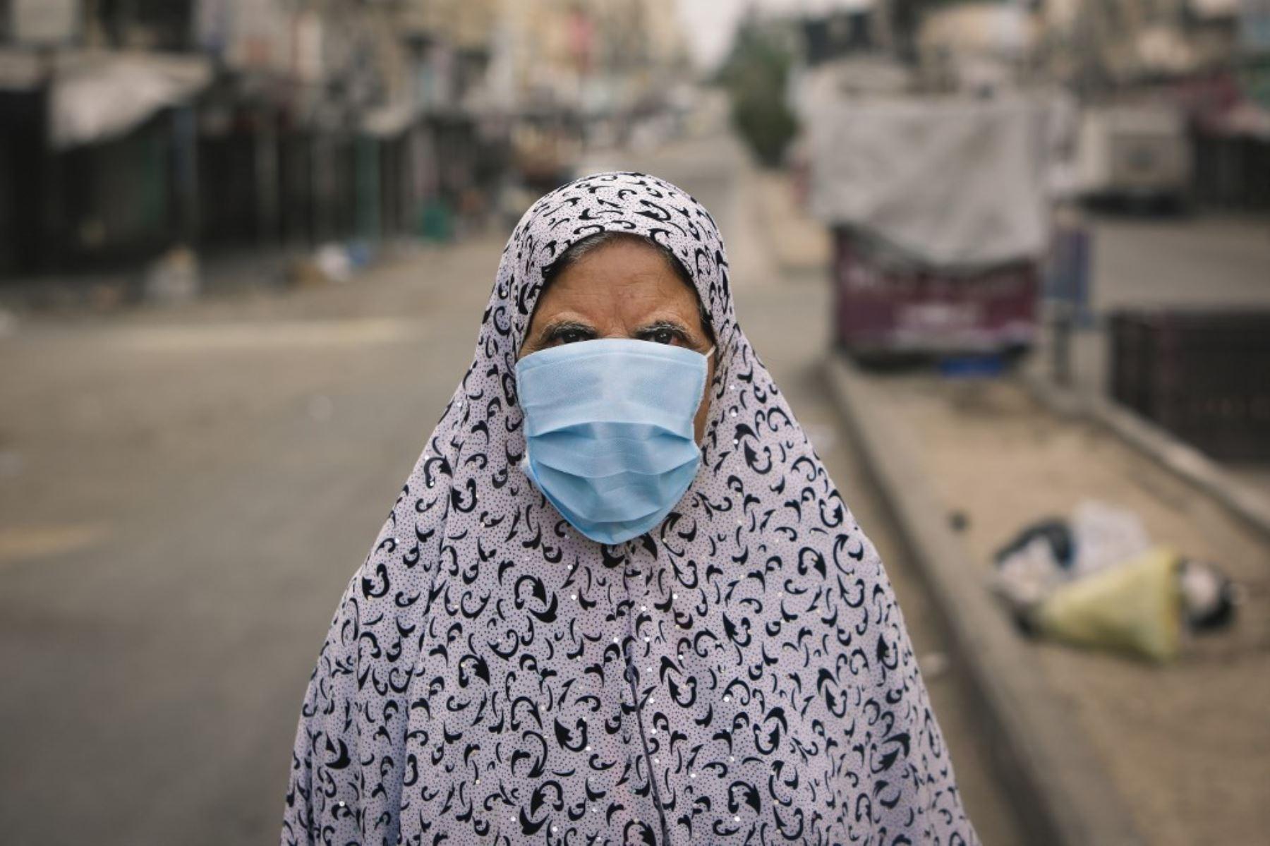 Una mujer palestina vestida con una máscara debido a la pandemia del coronavirus camina por una calle en la ciudad de Gaza. Foto: AFP