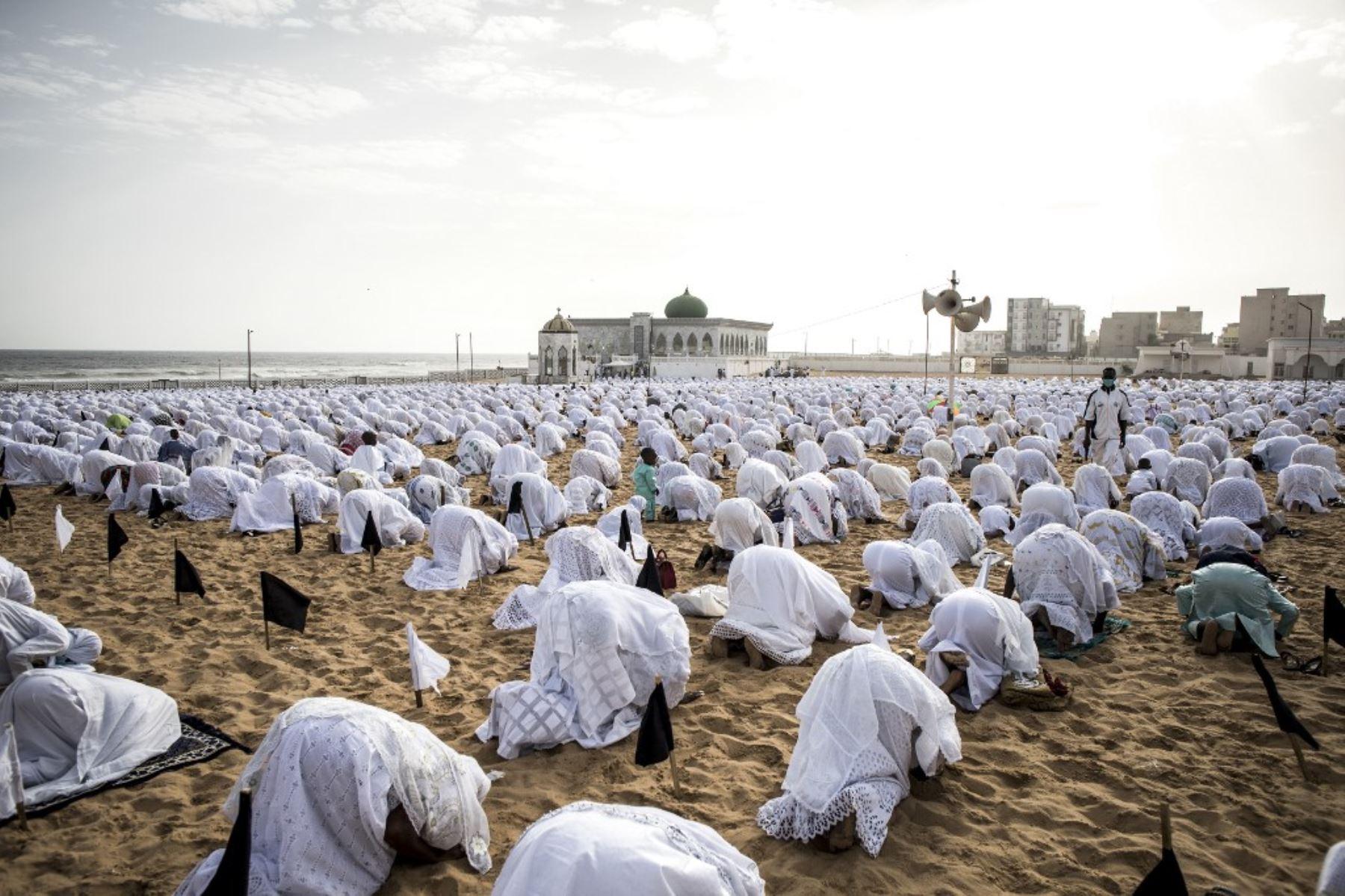 Los seguidores de la comunidad Layene con máscaras protectoras rezan en la playa frente a la Mezquita Yoff Layene, durante la festividad islámica de Korite en Dakar, Senegal. Foto: AFP