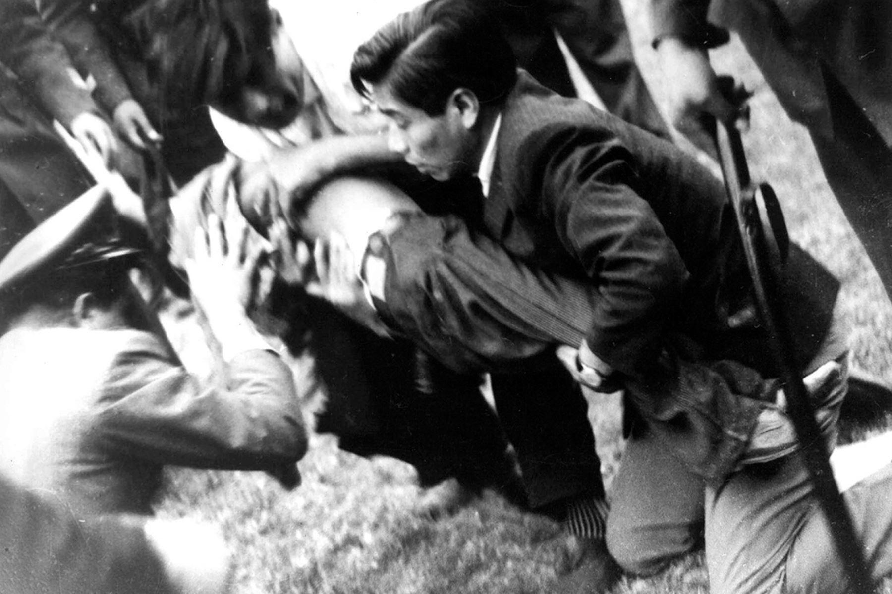 Lima - 24 mayo 1964. Un hombre herido recibe ayuda en el Estadio Nacional luego de un partido de clasificación para los Juegos Olímpicos de Tokio entre Perú y Argentina. La anulación de un gol peruano originó protestas e hizo que la policía  arrojara gases lacrimógenos al público generando caos y una estampida en la que murieron más de 300  personas. Foto:  AFP / IPD