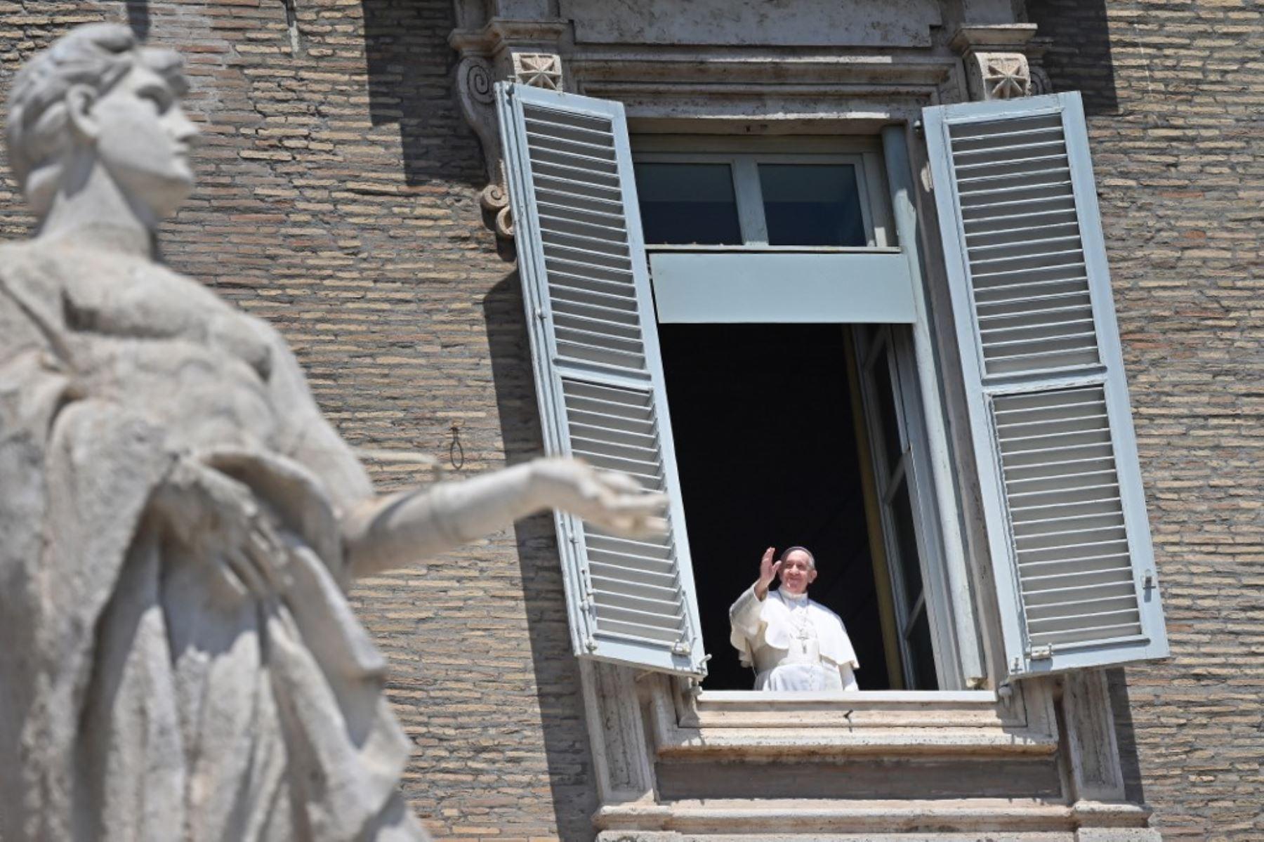 El Papa Francisco saluda desde la ventana del palacio apostólico con vista a una plaza vacía de San Pedro después de su transmisión en vivo de la oración del Ángelus este domingo. Foto: AFP