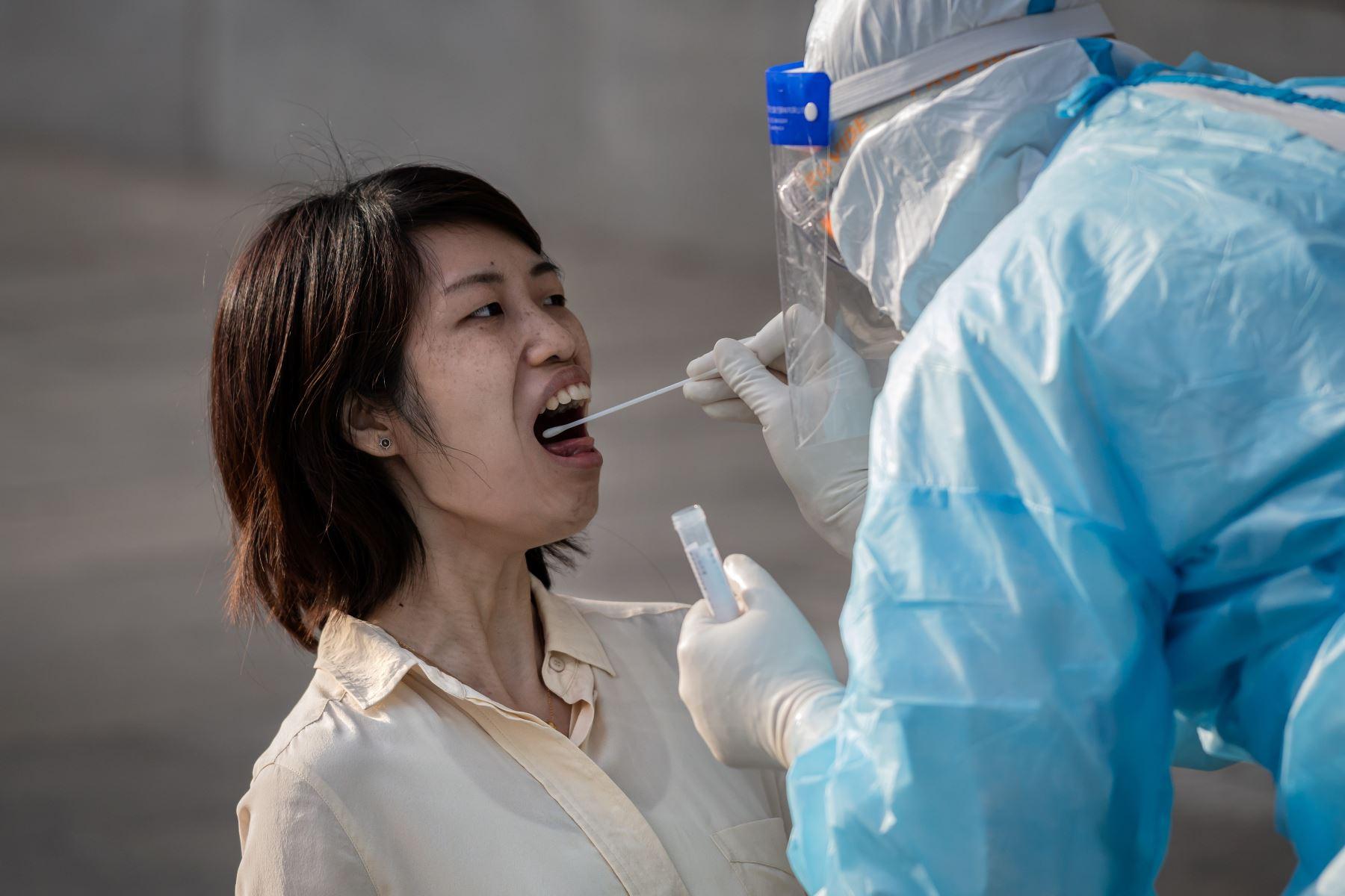 Un trabajador médico que usa equipo de protección completo toma una muestra de hisopo de una periodista para analizar el coronavirus COVID-19 en China. Foto: AFP