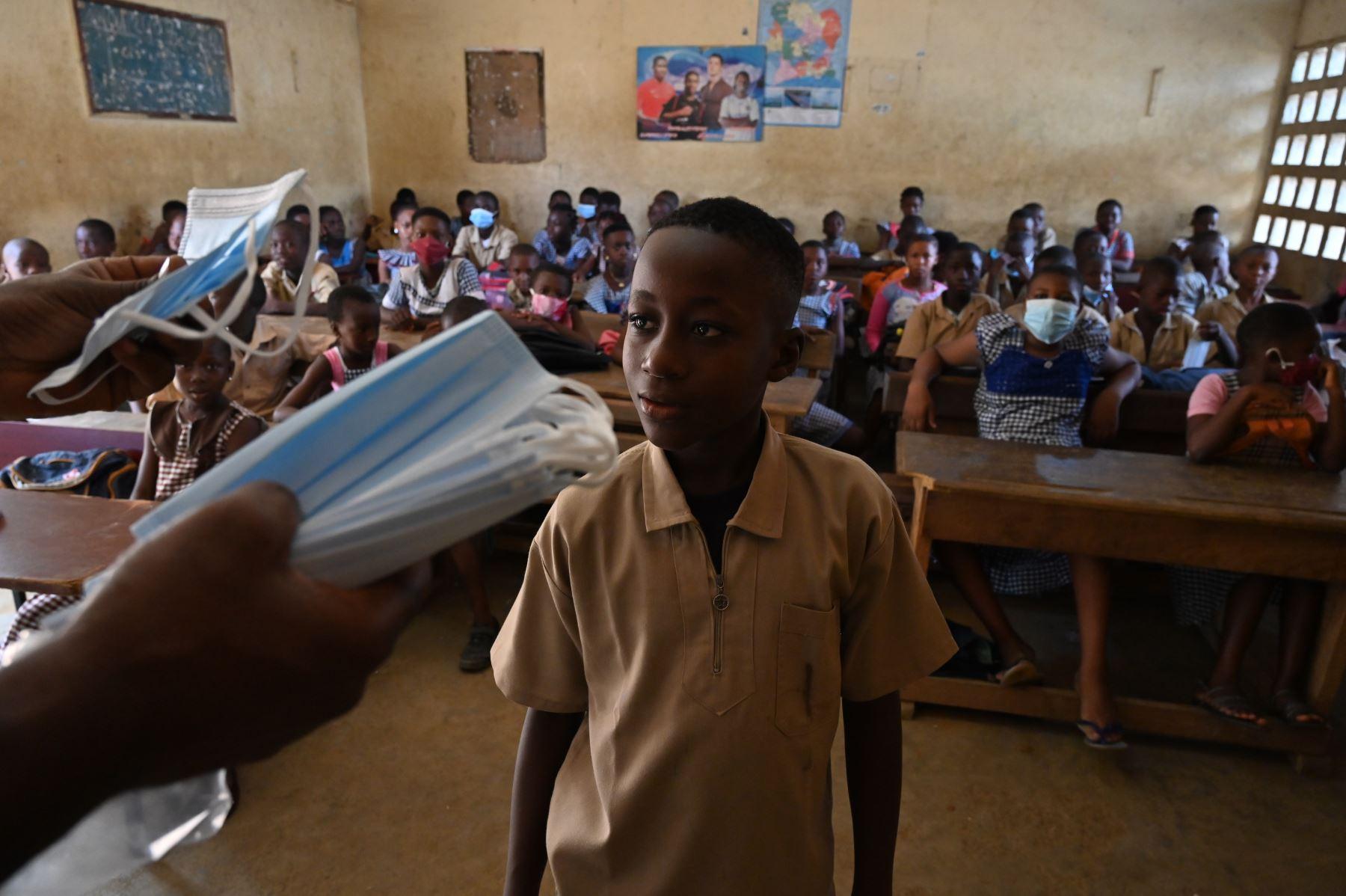Los escolares reciben máscaras faciales en el aula del director de una escuela primaria en el popular distrito de Attecoube en Abidjan. Foto: AFP