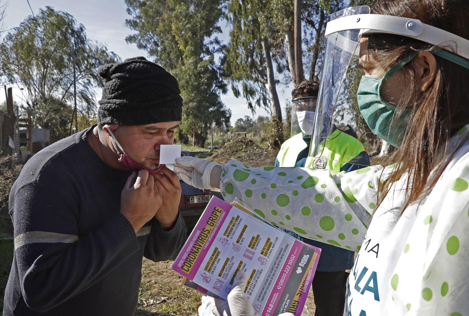 Un trabajador de la salud realiza una prueba olfativa -para controlar la pérdida de olfato- a un residente en el barrio Altos de San Lorenzo, cerca de la ciudad de La Plata, a 65 km de la ciudad de Buenos Aires, Argentina. Foto: AFP