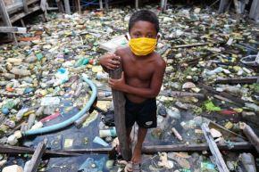 Un niño de la comunidad ribereña de Educandos usa una máscara facial durante la pandemia de coronavirus covid-19 en Manaos. Foto: AFP
