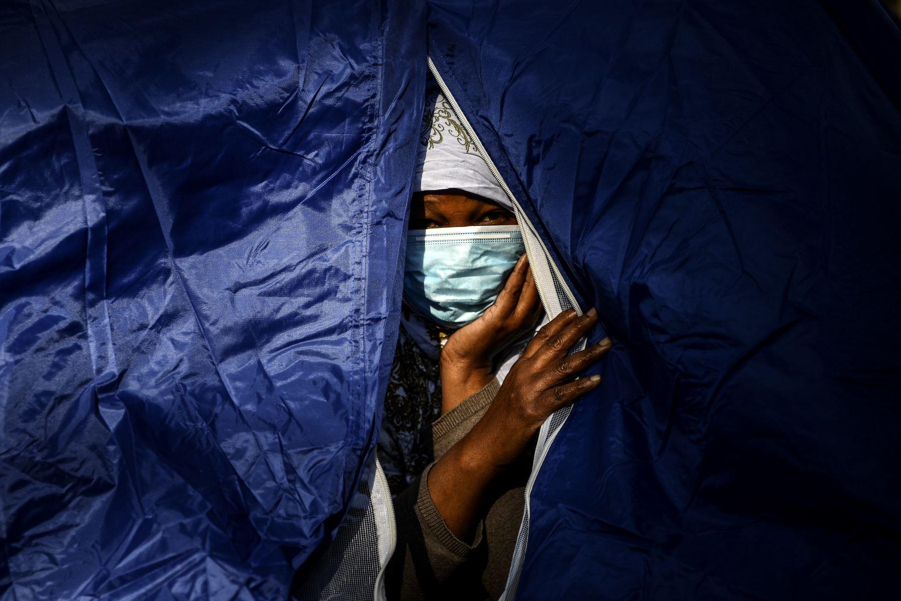 Una mujer somalí se asoma desde su tienda de campaña en un campamento improvisado establecido durante la noche por voluntarios de la organización benéfica Utopia 56 y que alberga a más de 50 migrantes, incluidos refugiados y solicitantes de asilo, a lo largo del Bassin de la Villette en París. Foto: AFP