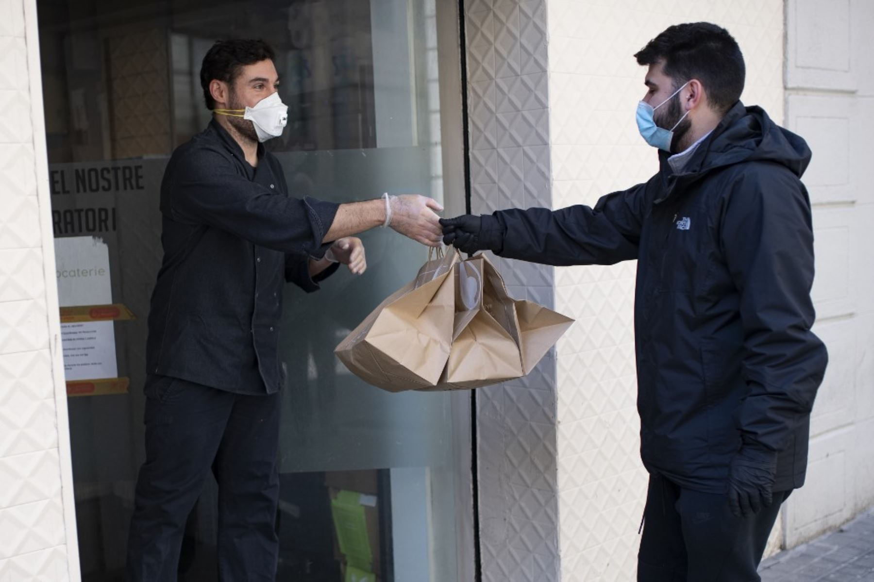 Un repartidor que trabaja para Delivery4Heroes llega a un restaurante para recoger bolsas con alimentos para el personal sanitario que se enfrenta al nuevo coronavirus en Barcelona. Foto: AFP