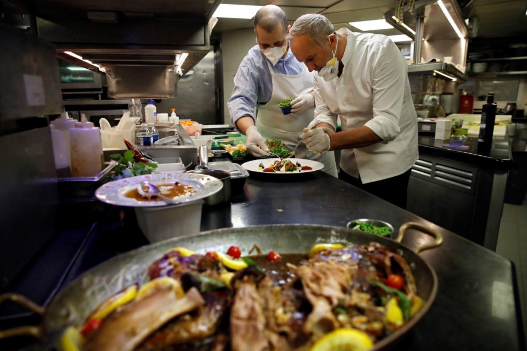 """El chef francés de 3 estrellas Christian Le Squer y el chef de una estrella Alan Taudon cocinan para empleados de un hospital parisino en la cocina del restaurante """"Le Cinq"""" en el hotel Four Season George V Palace en París. Foto: AFP"""