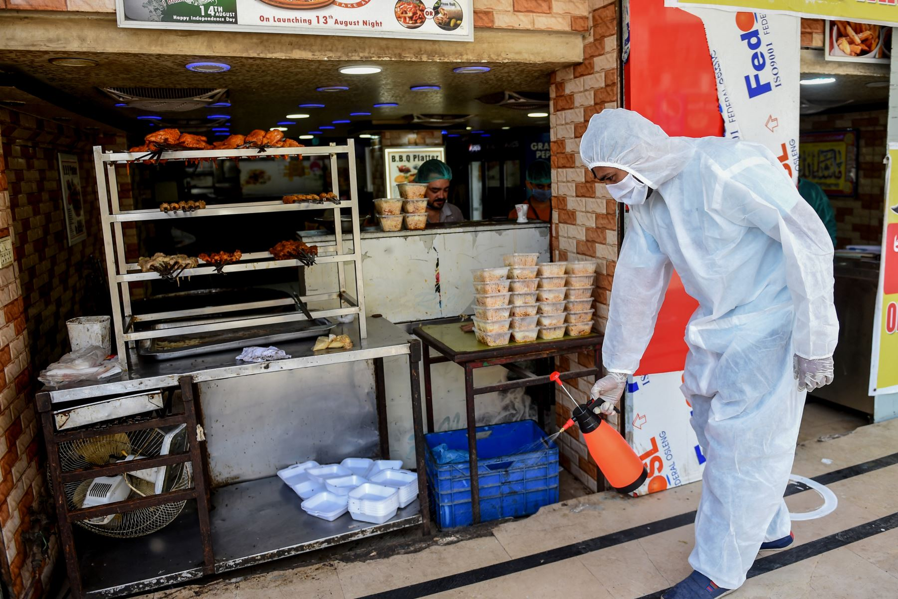 Un empleado rocía desinfectante fuera de un restaurante abierto para llevar y servicios de entrega durante un bloqueo nacional impuesto por el gobierno como medida preventiva contra el coronavirus COVID-19, en Pakistan. Foto: AFP