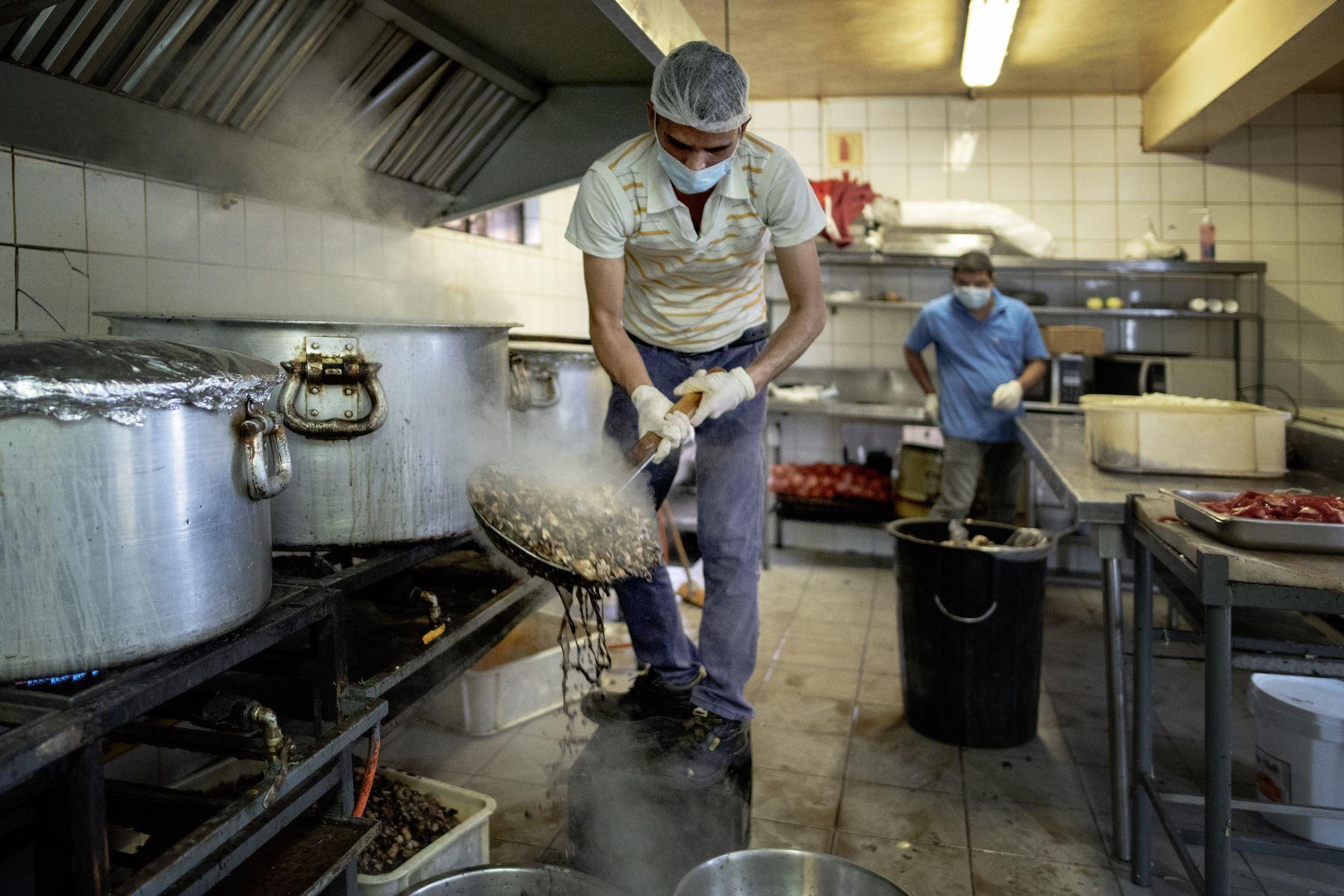 Un trabajador de la cocina prepara comidas calientes en el restaurante indio Thava, en The Gardens, para la distribución diaria de alimentos en un asentamiento informal en Tembisa, Johannesburgo. Foto: AFP