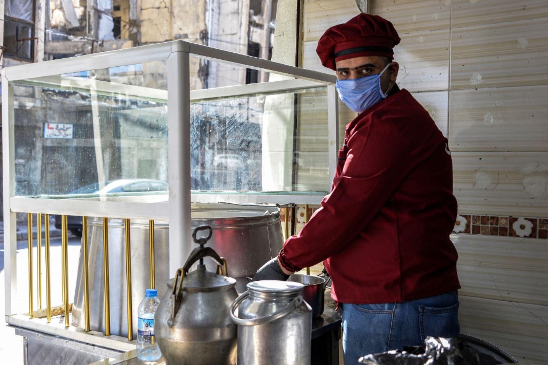 """Un cocinero que usa una máscara quirúrgica en un restaurante que sirve """"pacha"""", un plato tradicional local tradicional en Mosul, Irak. Foto: AFP"""