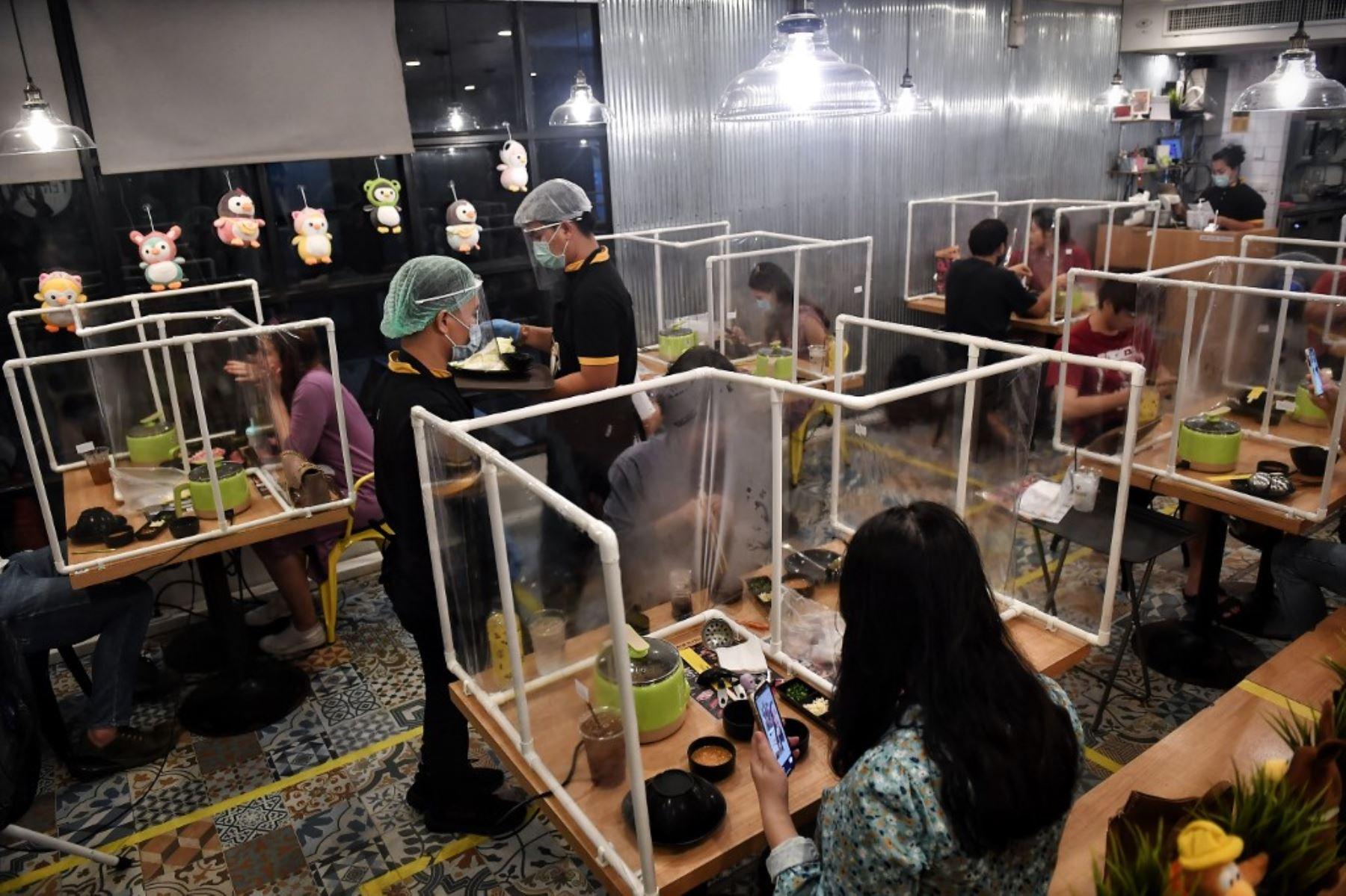 La gente come entre particiones plásticas, configuradas en un esfuerzo por contener cualquier propagación del coronavirus COVID-19, en el restaurante Penguin Eat Shabu en Bangkok. Foto: AFP