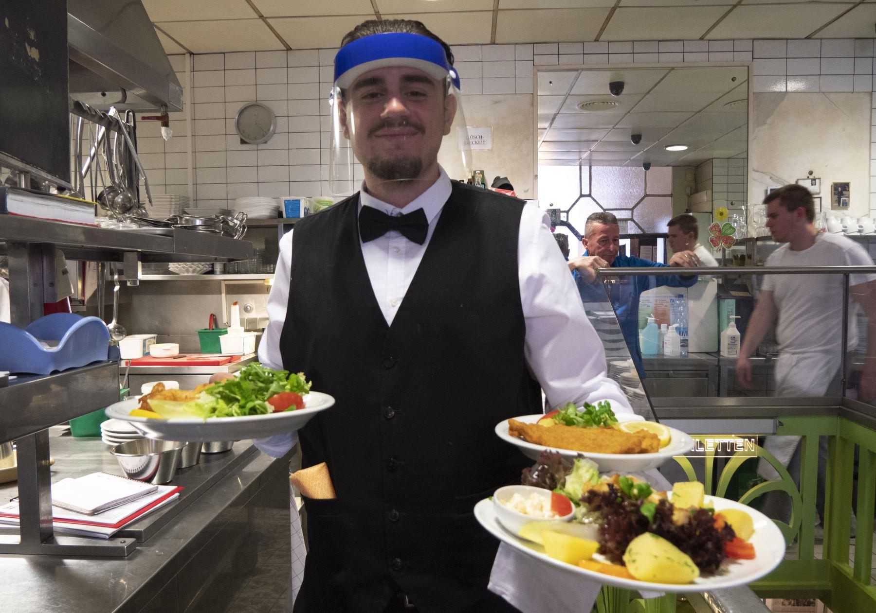 Un camarero usa un protector facial mientras atiende a los clientes en el Café Prueckel en Viena, Austria. Foto: AFP