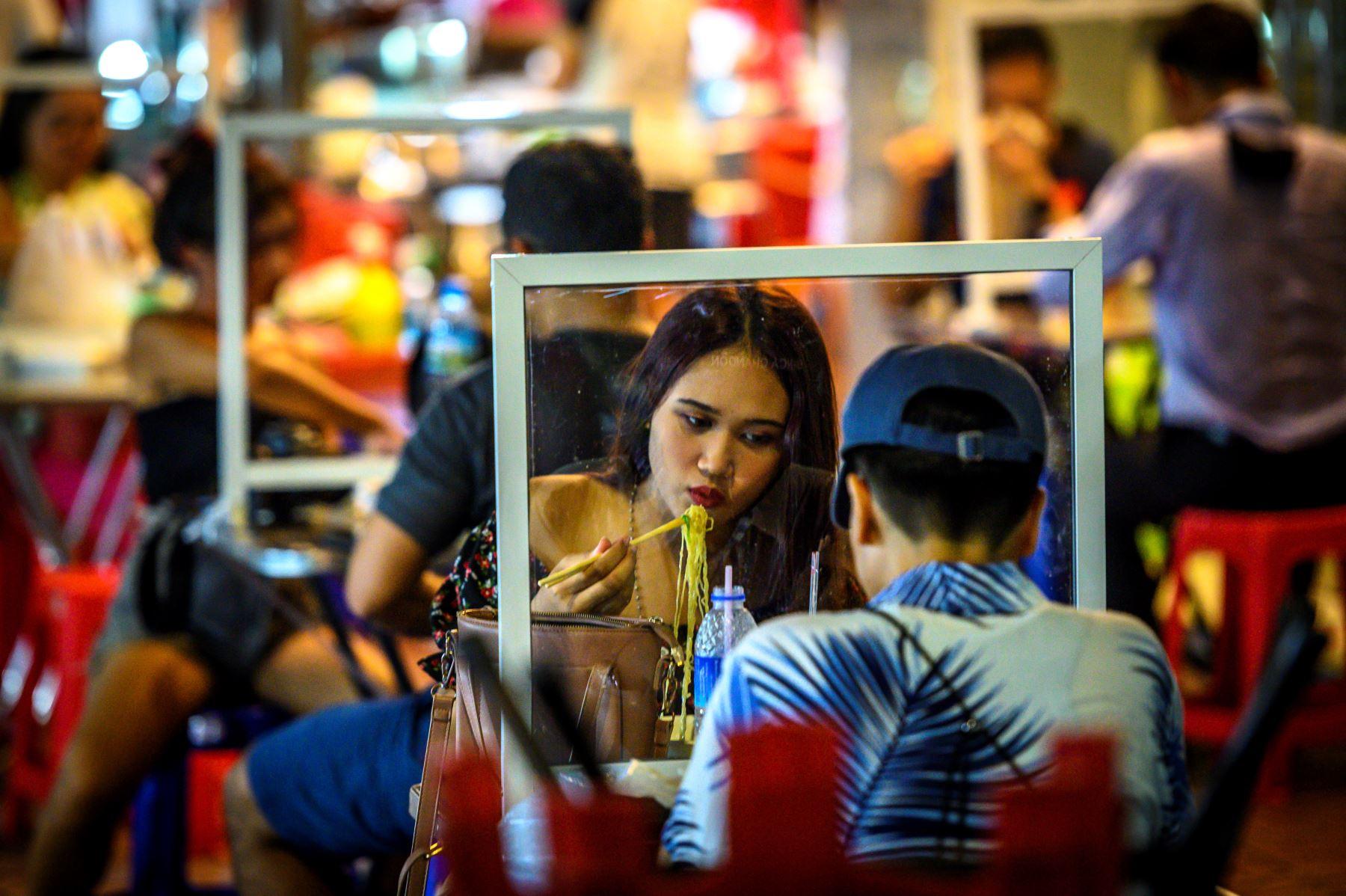 La gente come en un restaurante callejero que implementa el distanciamiento social con divisores de plástico, en Tailandia. Foto: AFP