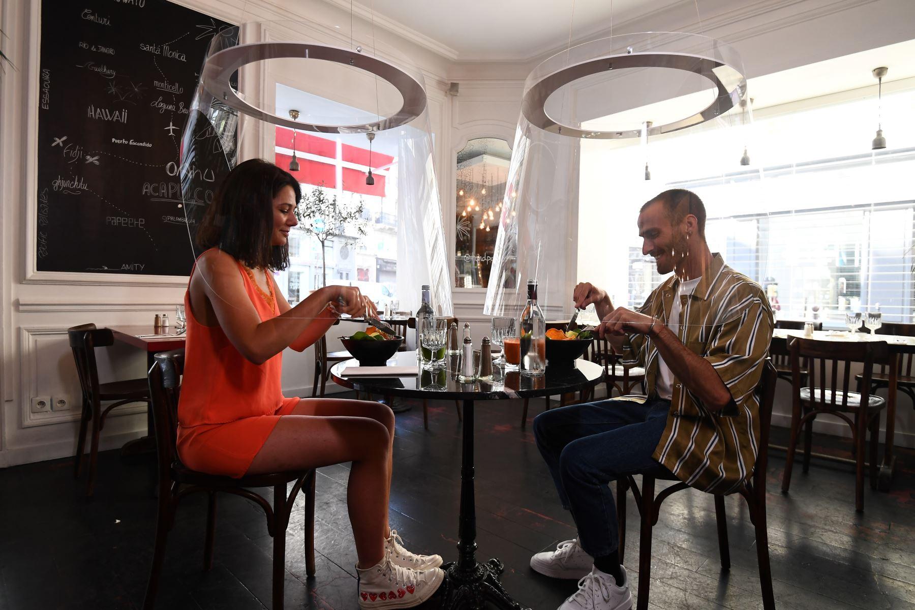 Una pareja almuerza bajo la protección de plexiglás diseñada por Christophe Gernigon en el restaurante H.A.N.D, en París. Foto: AFP