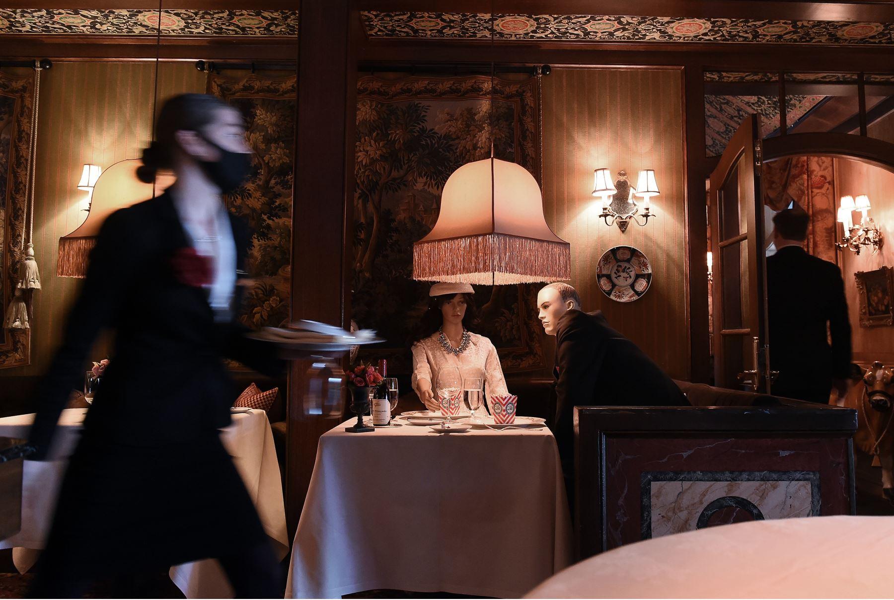 Una camarera usa una máscara facial cuando pasa delante de los maniquíes que pueblan el comedor de The Inn at Little Washington, uno de los restaurantes más reconocidos del país. Foto: AFP