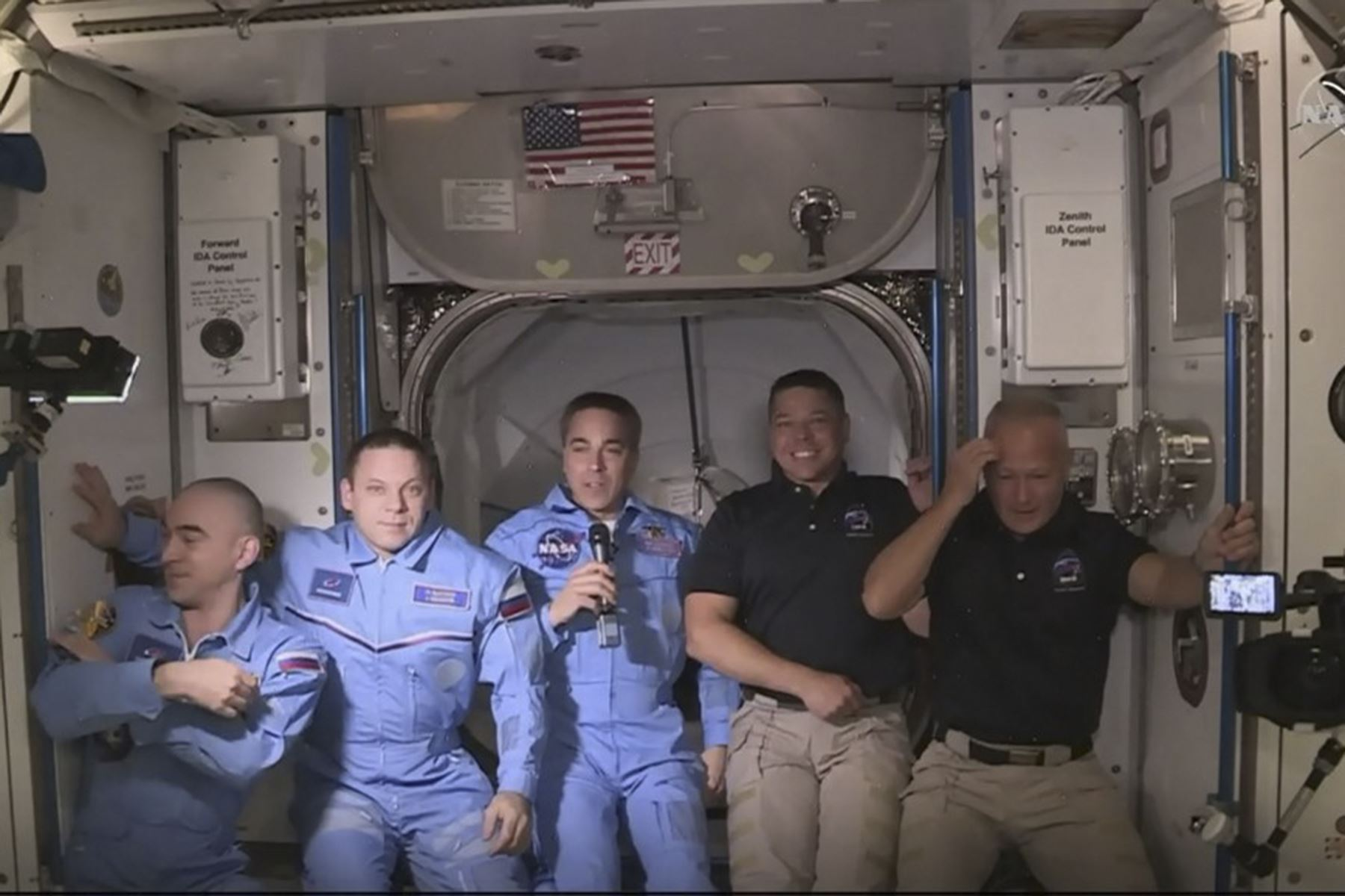 Esta imagen de captura de fotogramas de la NASA muestra a los astronautas de la NASA Crew Dragon de SpaceX Douglas Hurley (L) y Robert Behnken (R) llegando después de que la escotilla se abrió a la Estación Espacial Internacional el 31 de mayo de 2020 con otros astronautas. Foto: AFP
