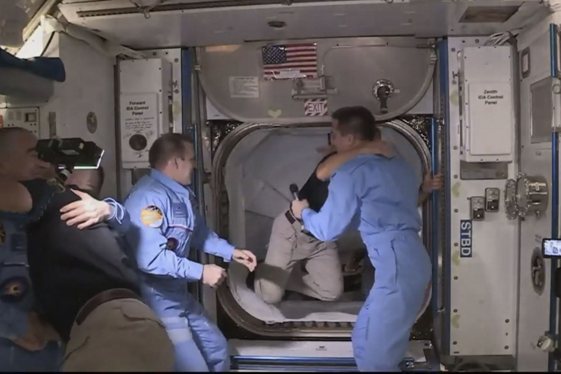 Esta imagen de captura de fotogramas de la NASA muestra a los astronautas de la NASA Crew Dragon de SpaceX Douglas Hurley (I) y Robert Behnken (D) llegando después de que la escotilla se abrió a la Estación Espacial Internacional el 31 de mayo de 2020 con otros astronautas. Foto: AFP