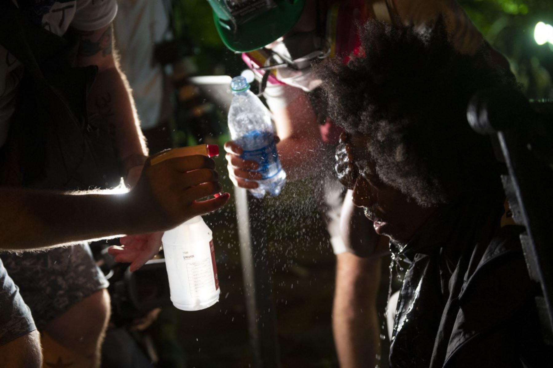 Los manifestantes se rociaron agua en los ojos después de que la policía disparó gases lacrimógenos durante una protesta contra la muerte de George Floyd cerca de la Casa Blanca en Washington, DC. Foto: AFP
